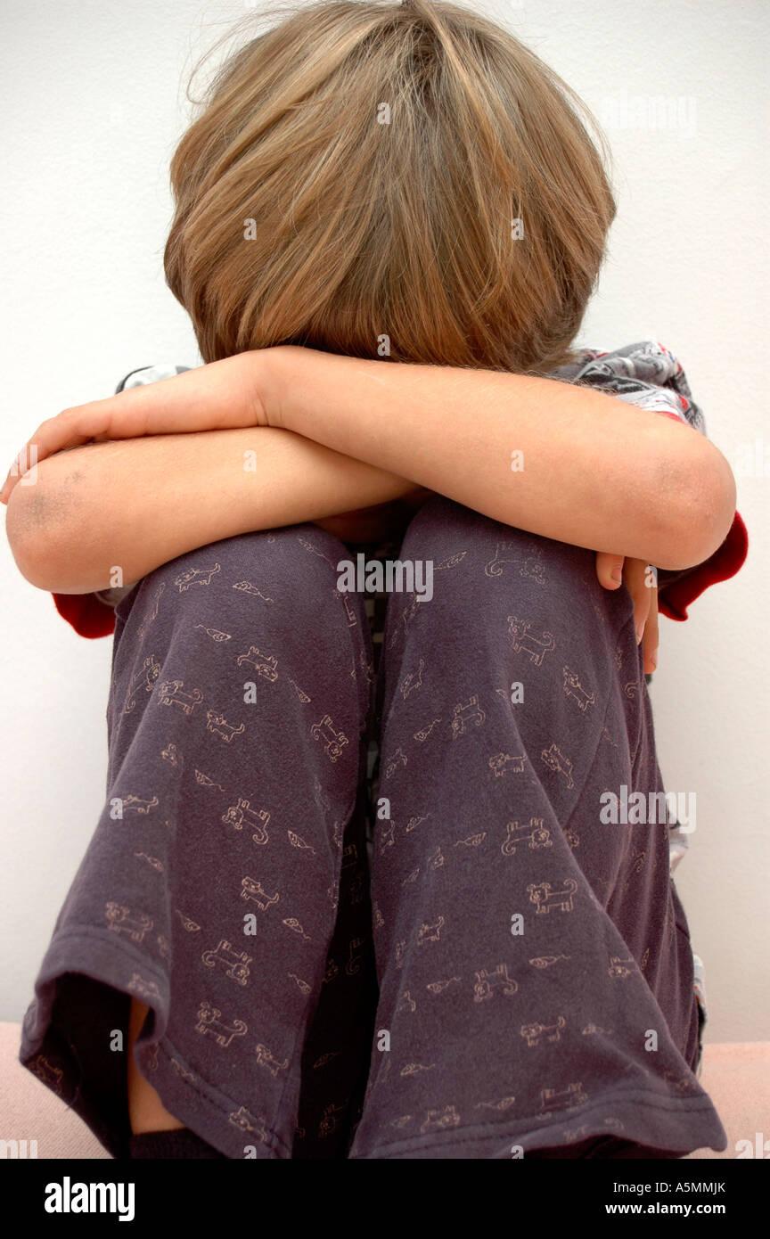 Symbolbild Kindesmissbrauch zusammengekeuaerter Junge symbolic for child molestation Kind Menschen Mensch Personen Leute people Stock Photo