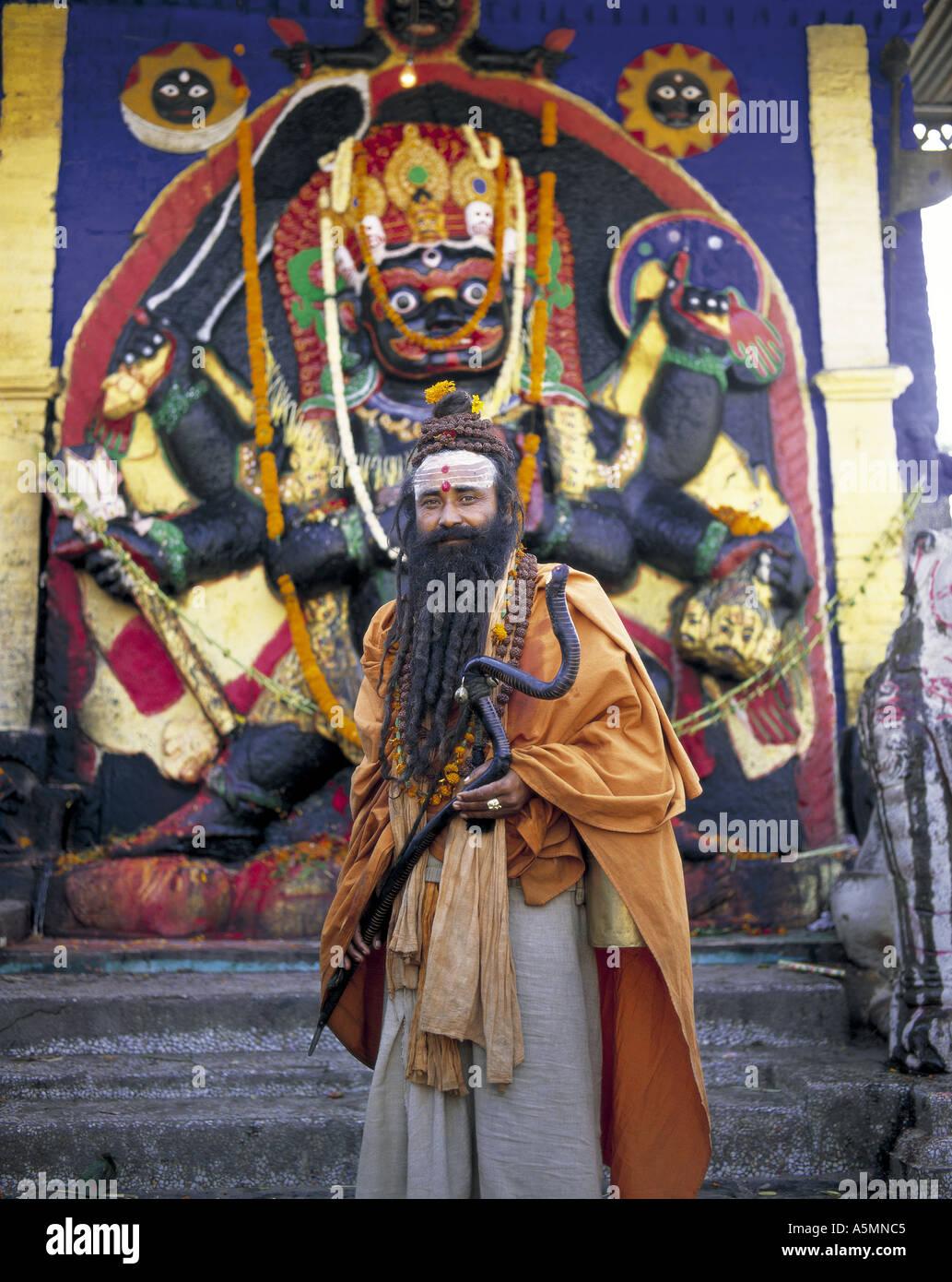 Sadhu standing in front of Goddess Kali statue Katmandu Nepal - Stock Image
