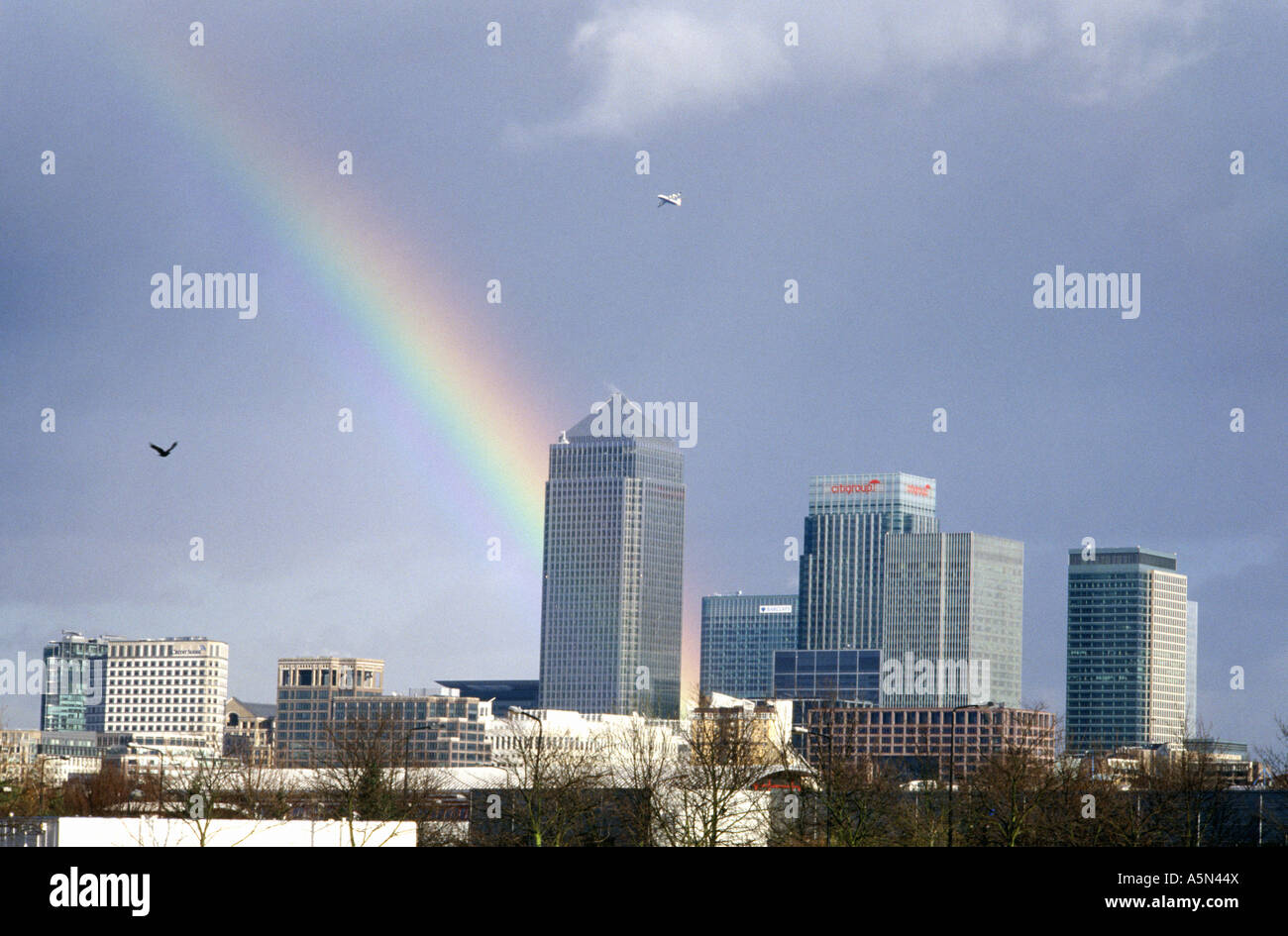 canary wharf with a rainbow going into it london uk - Stock Image