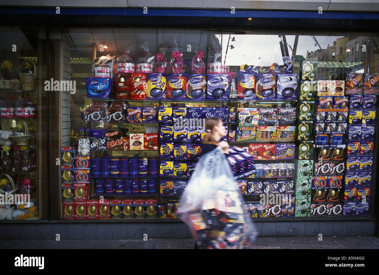 A Girl With A Bag Full Of Easter Eggs Walks Past A Shop Full Of Stock Photo Alamy