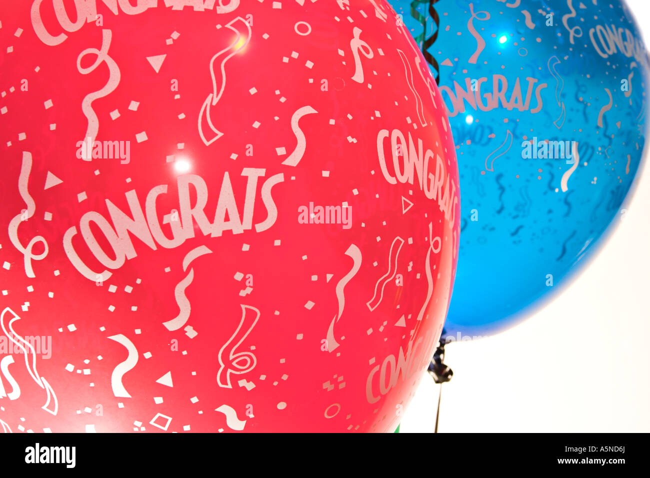 Party Time congratulations Blue and red balloons with streamers and CONGRATS written on them cutout - Stock Image