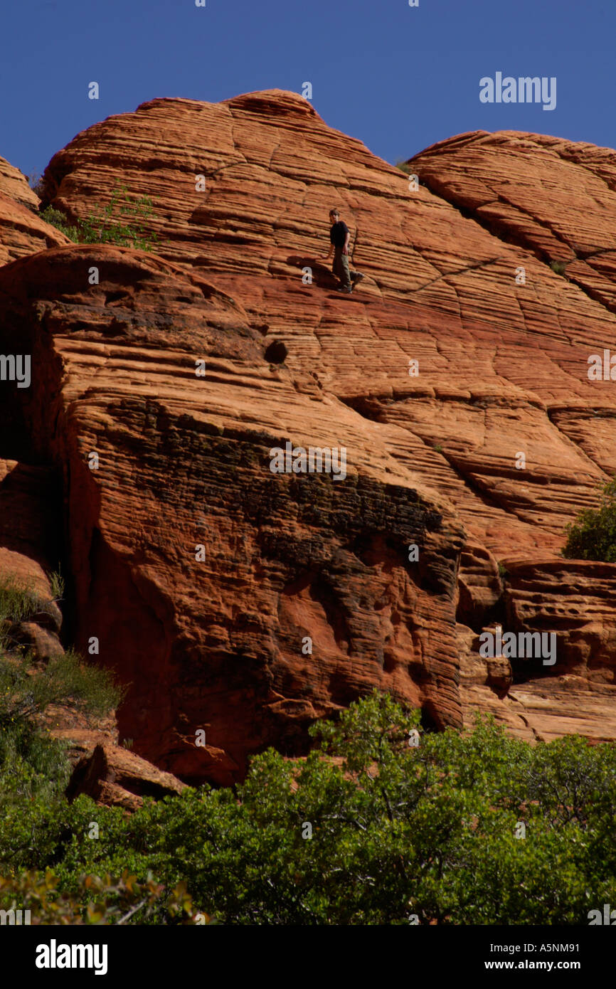 teenager standing on steep incline of red layered sandstone formation - Stock Image