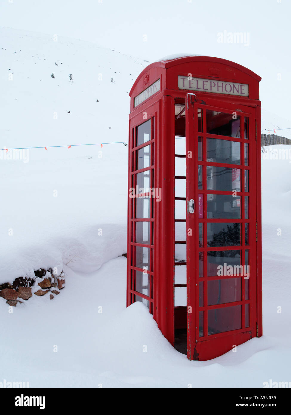 Old fashioned red telephone box K6 with door open in deep winter snow on Cairngorm mountain Cairn Gorm Highland Scotland UK - Stock Image