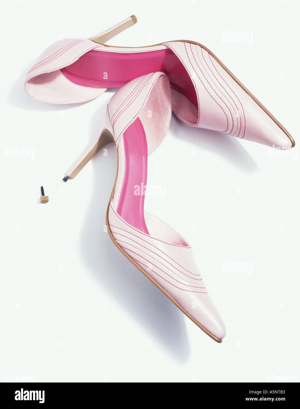 A pair of pink stiletto shoes one with the heel tip missing - Stock Image