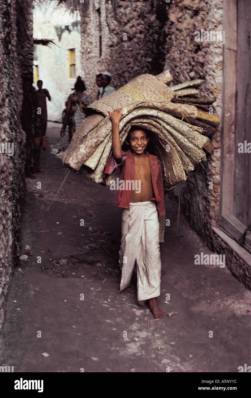 Young boy carrying mats Pate Island Lamu archipelago Kenya coast East Africa - Stock Image