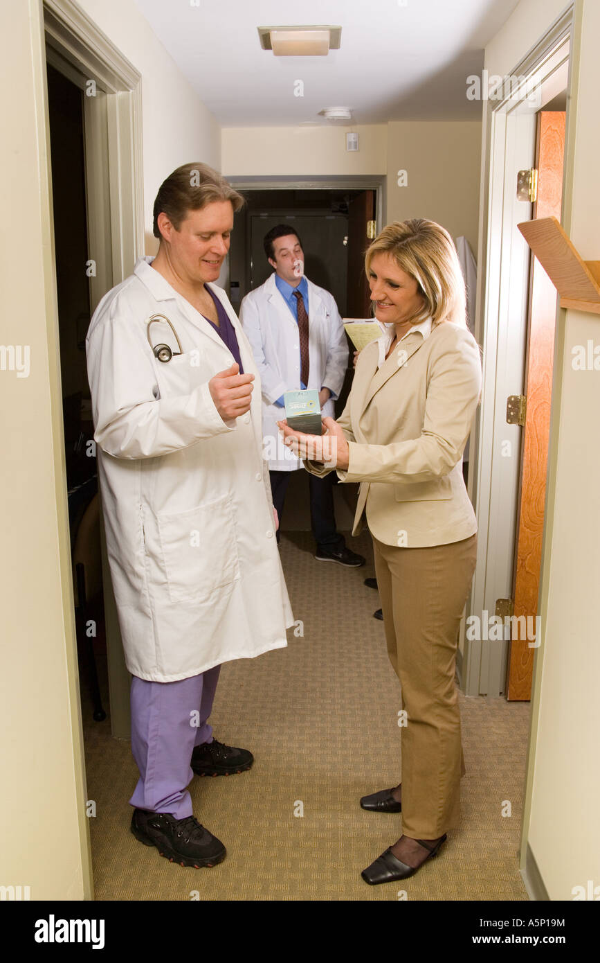 medical sales pharma rep shows a doctor samples in the hallway of the doctors office