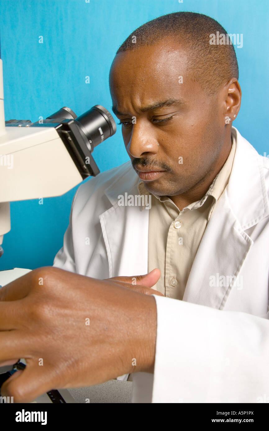 Black male scientist uses microscope. - Stock Image