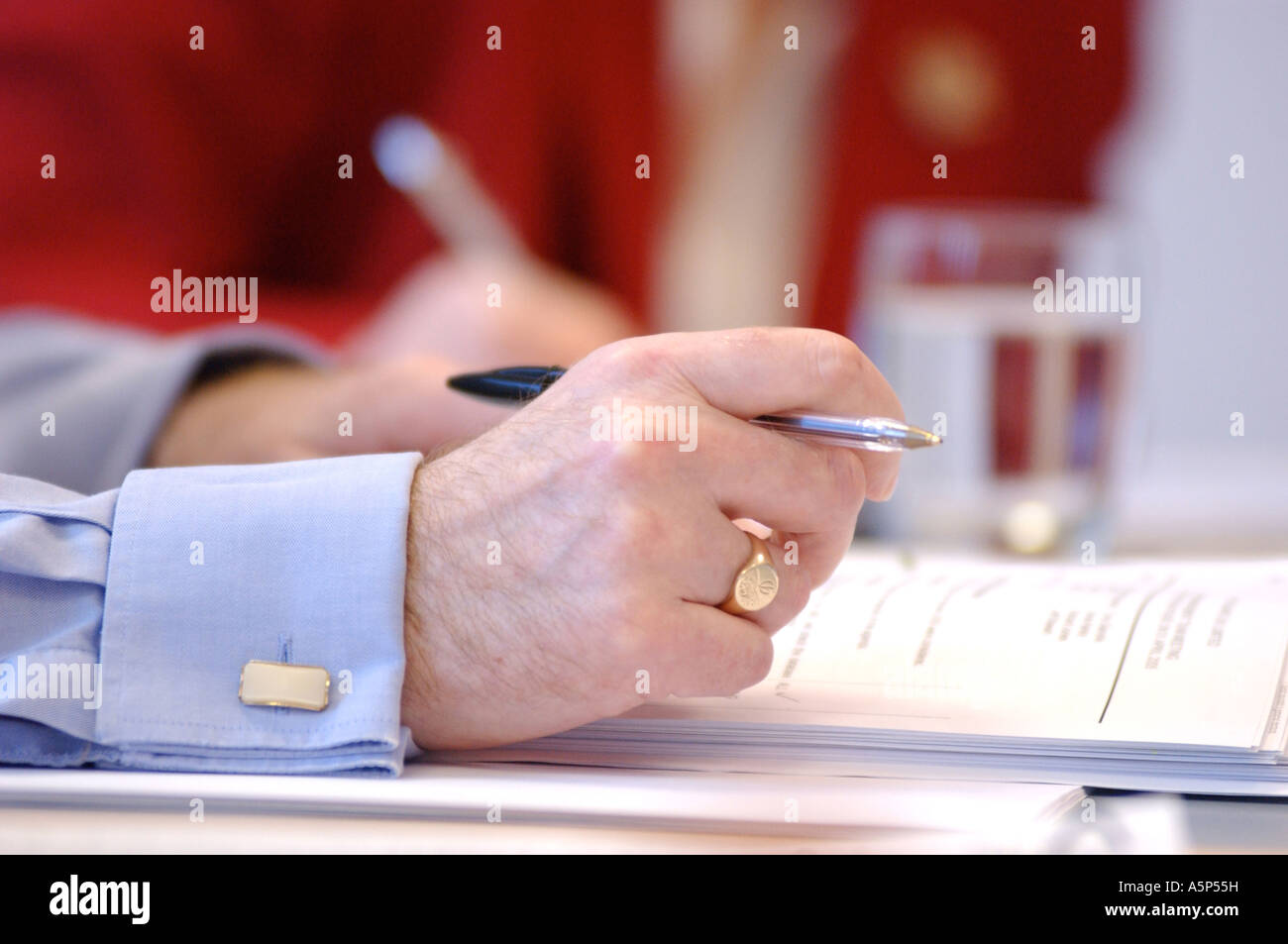 British business man writing in meeting London UK - Stock Image