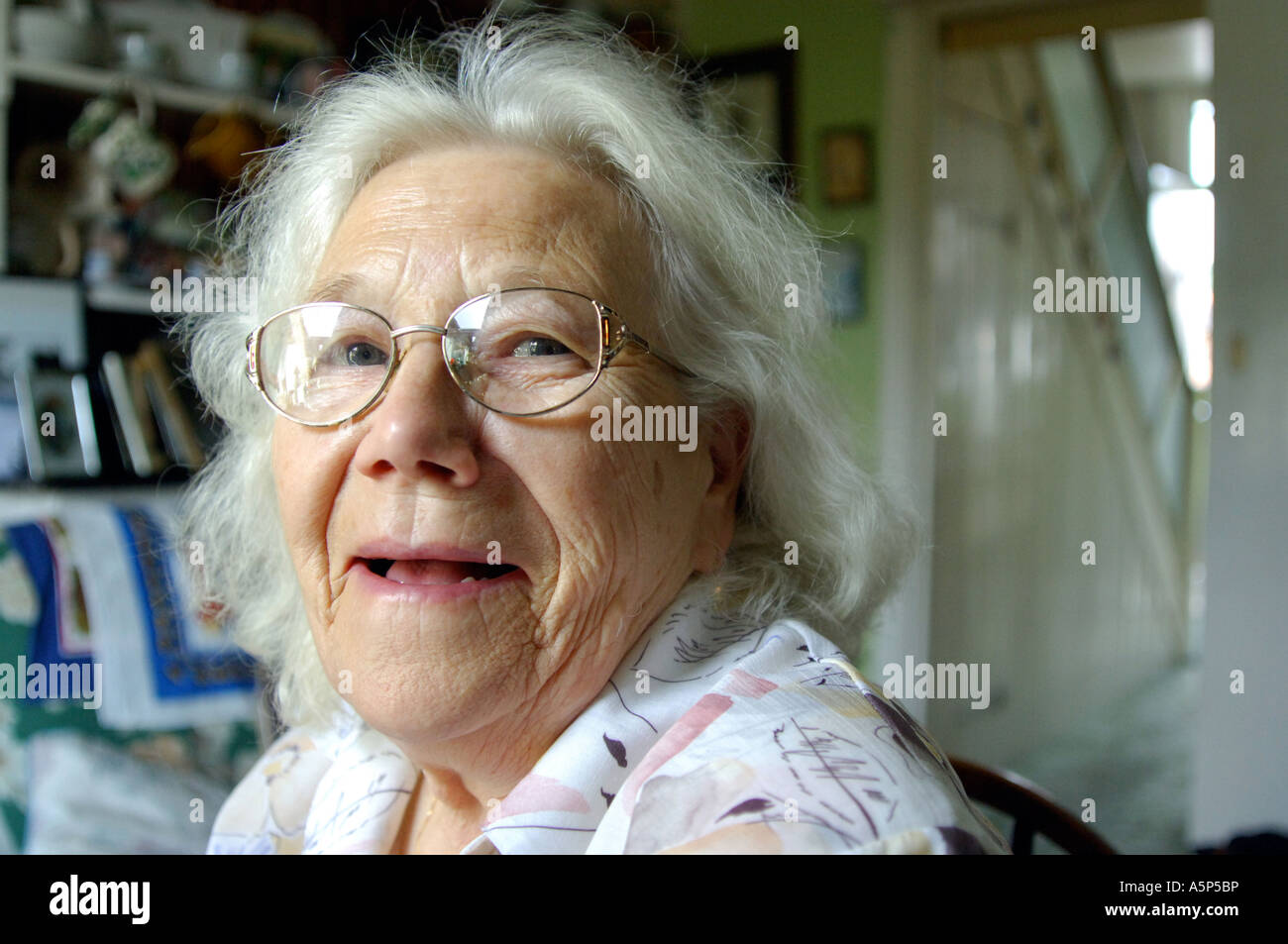 Portrait of a happy smiling British pensioner at her home in London UK - Stock Image