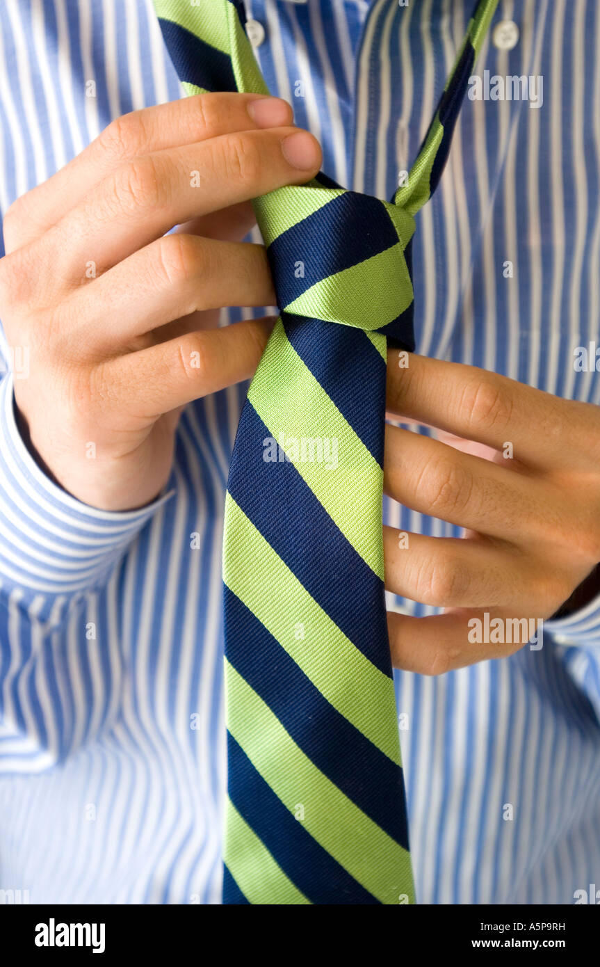 Hands making knot in striped tie. - Stock Image