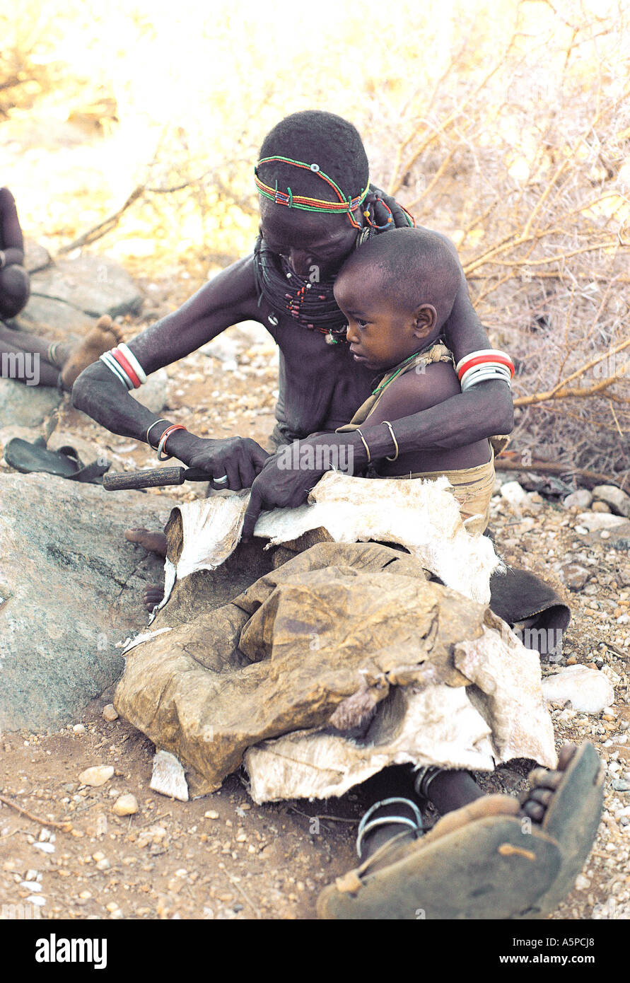Rendille woman with her baby She is sewing leather skirts from new skins Korr northern Kenya East Africa - Stock Image
