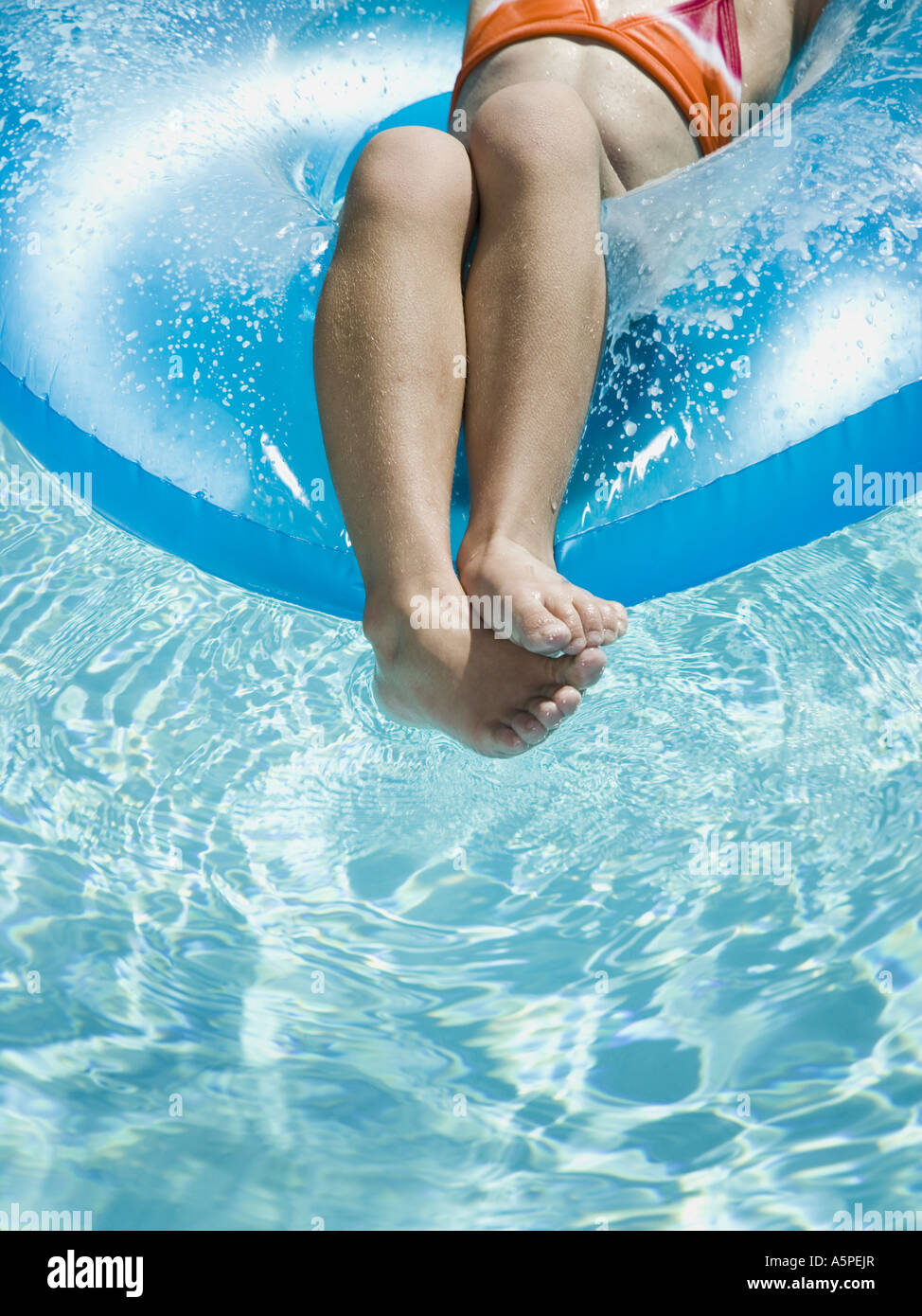 Young girl floating on life ring in swimming pool Stock Photo