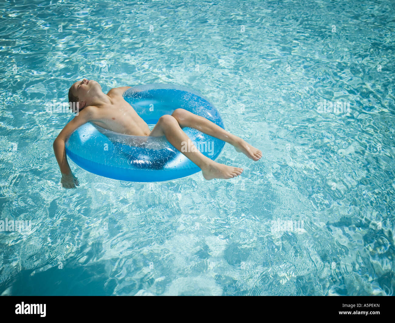 Young boy floating on life ring in swimming pool Stock Photo
