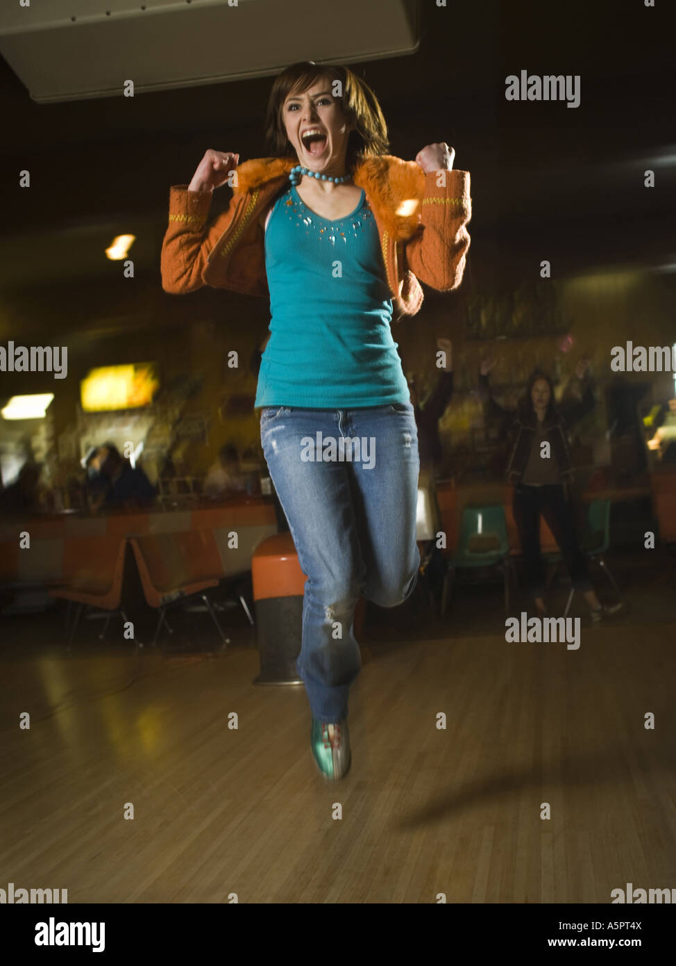Teenage girl jumping in excitement in a bowling alley - Stock Image