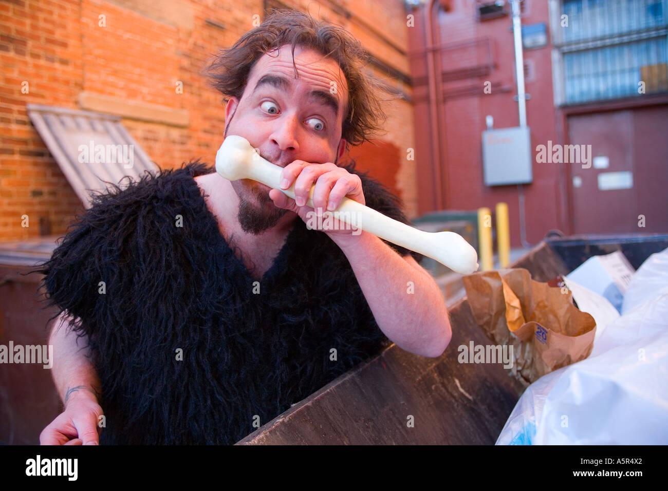 man dressed as caveman eating bone in alleyway - Stock Image