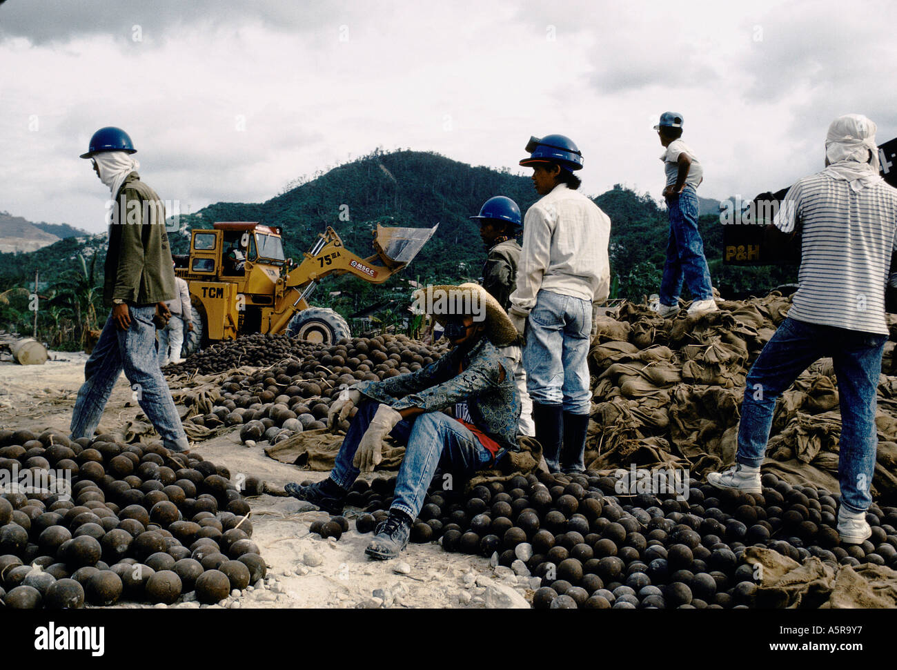 MOUNT PINATUBO DISASTER FEBRUARY 1991 WORKERS AT THE BENQUET CO COPPERMINE ZAMBALES PROVINCE ARE LOADING STEEL BALLS FOR THE CR - Stock Image
