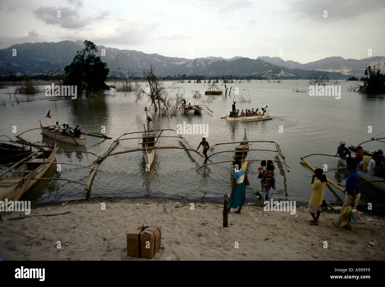 MOUNT PINATUBO DISASTER FEBRUARY 1991 A VIEW OF THE LAKE PINATUBO LOCALS WITH GOODS CROSS THE LAKE WITH SHALLOW BOATS AS IT IS - Stock Image