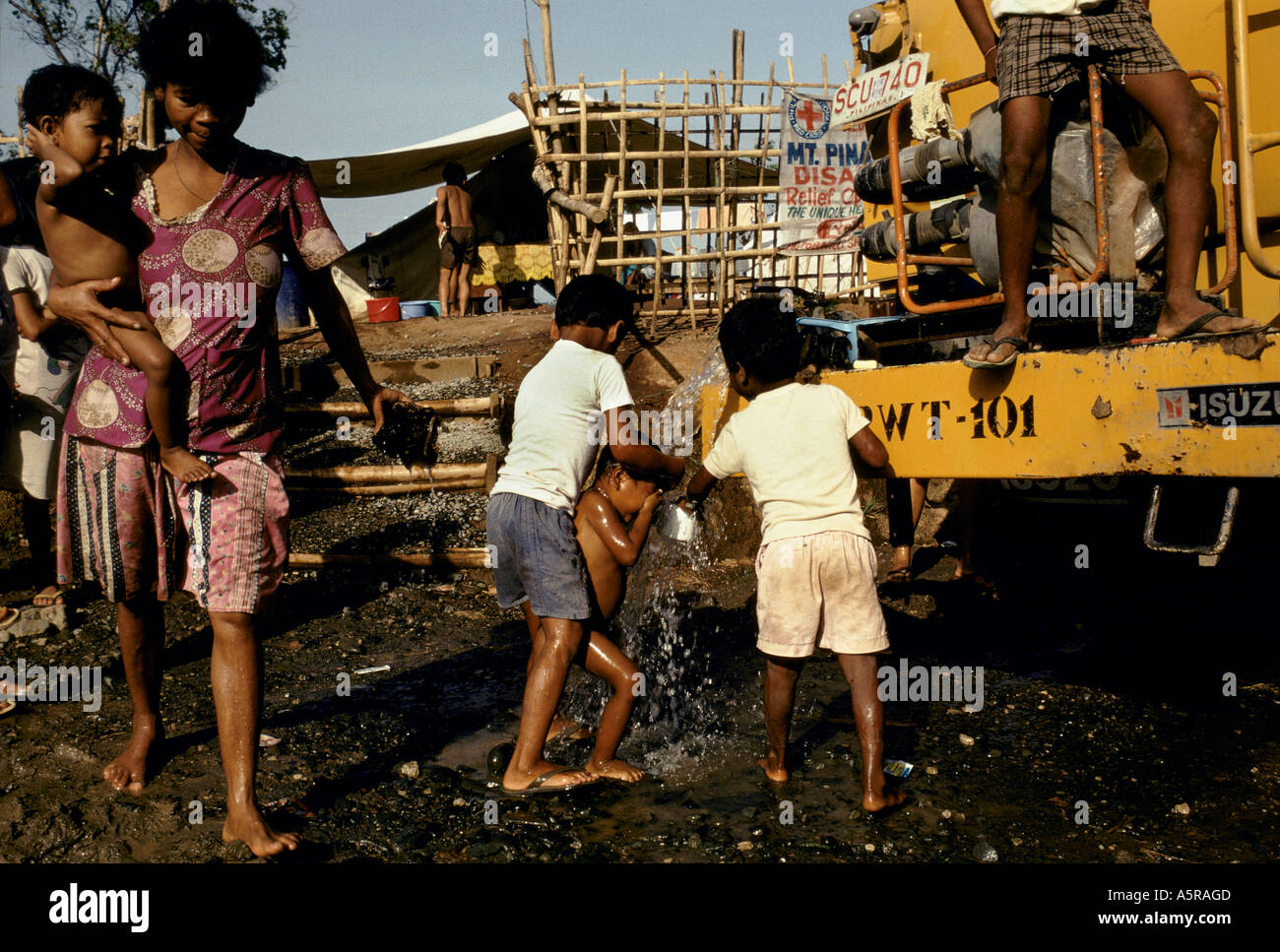 MOUNT PINATUBO DISASTER FEBRUARY 1991 A YOUNG CHILD IS WASHED BY OLDER CHILDREN AS FRESH WATER IS DELIVERED TO THE CAMP - Stock Image
