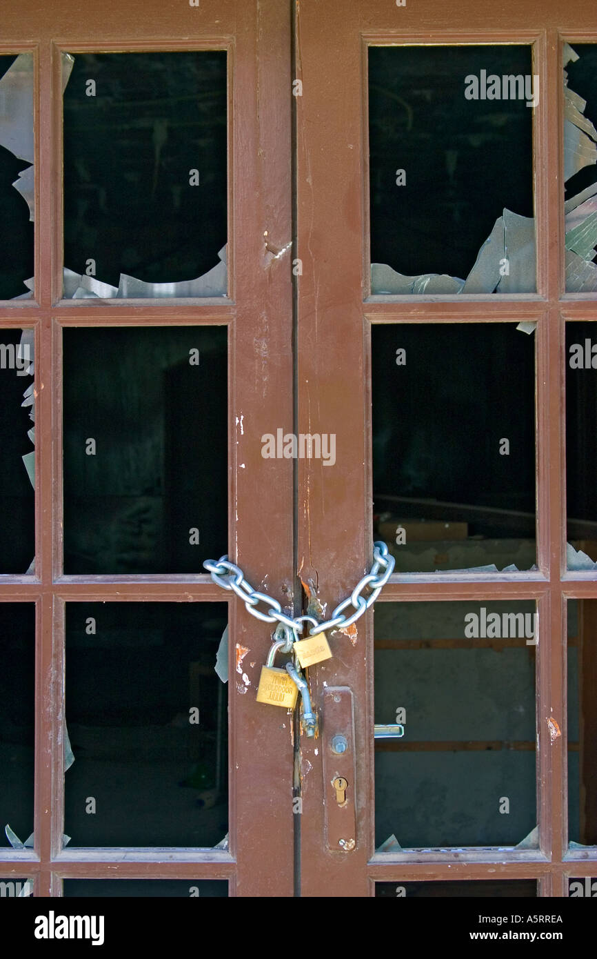 Chain and lock on door with smashed glass Stock Photo
