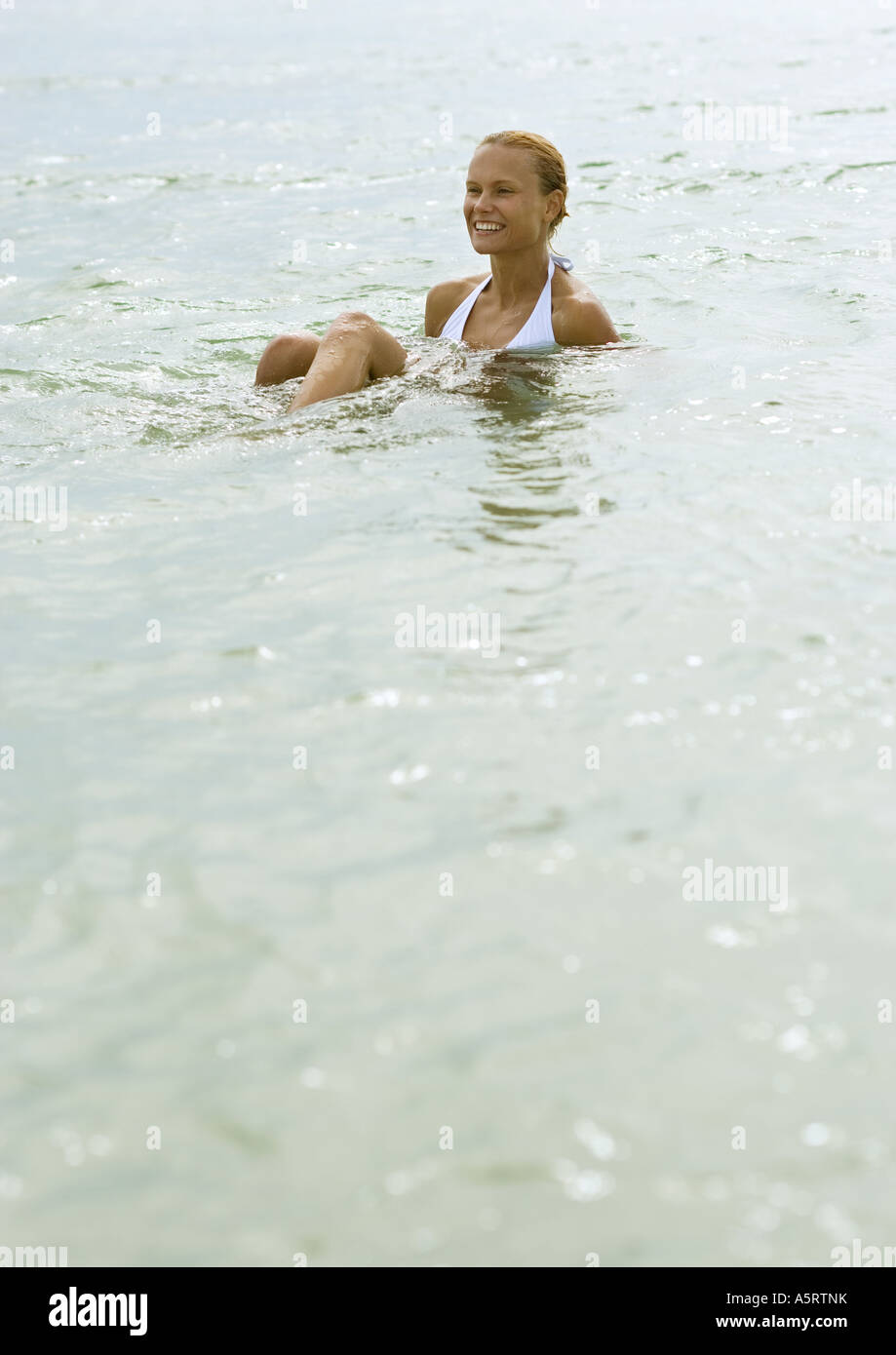 Woman sitting in shallow water - Stock Image