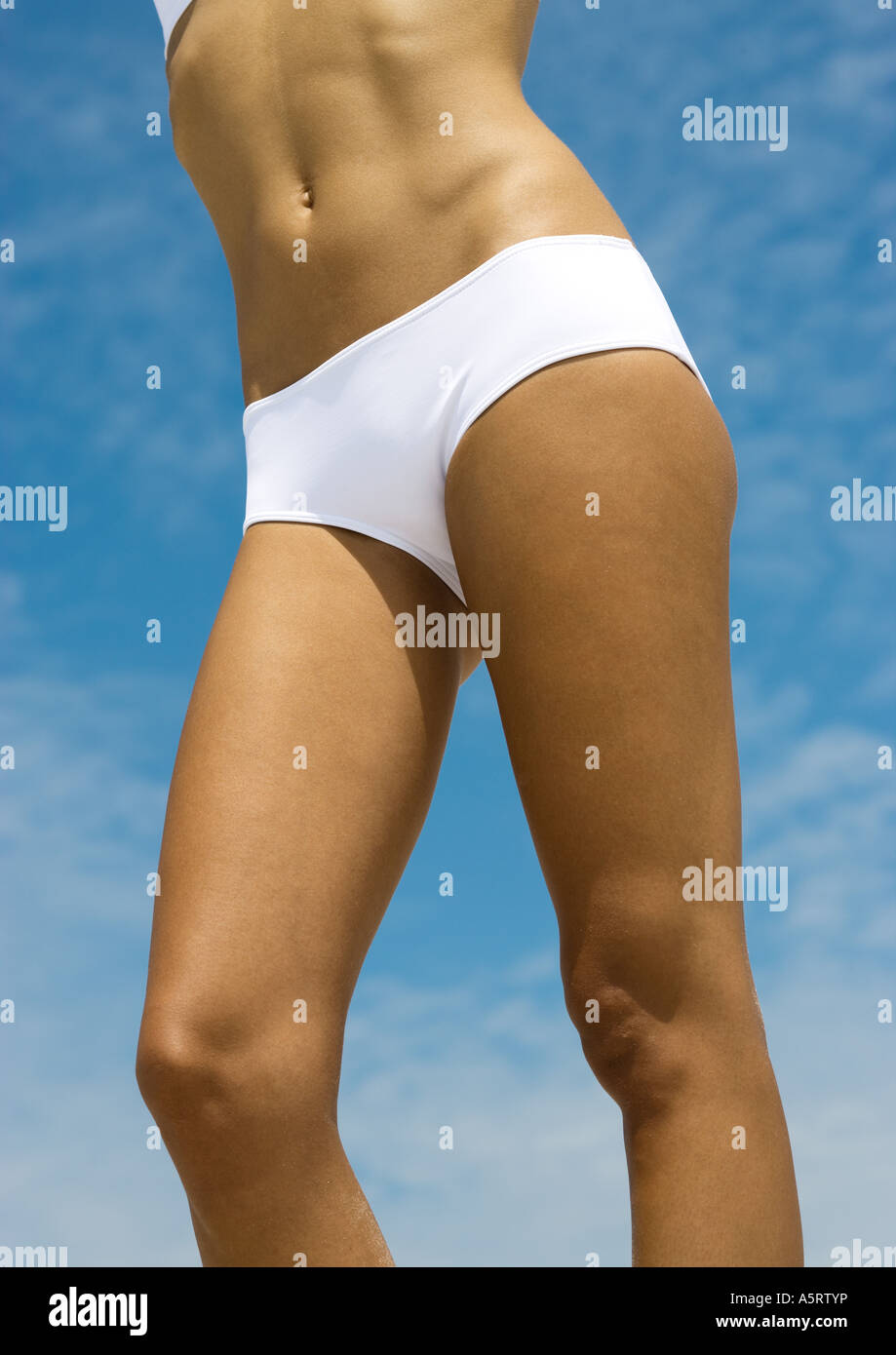 Woman in bikini, mid section, sky in background - Stock Image