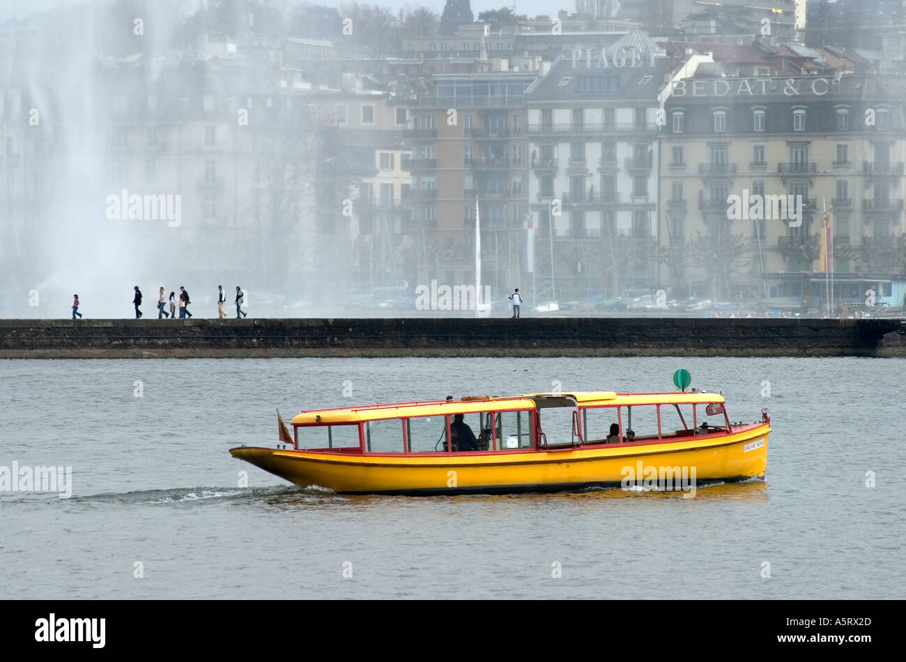 Ferry boat on Lac Geneva View across the lake to the splashes of the giant fountain Jet d Eau Geneva Switzerland Stock Photo