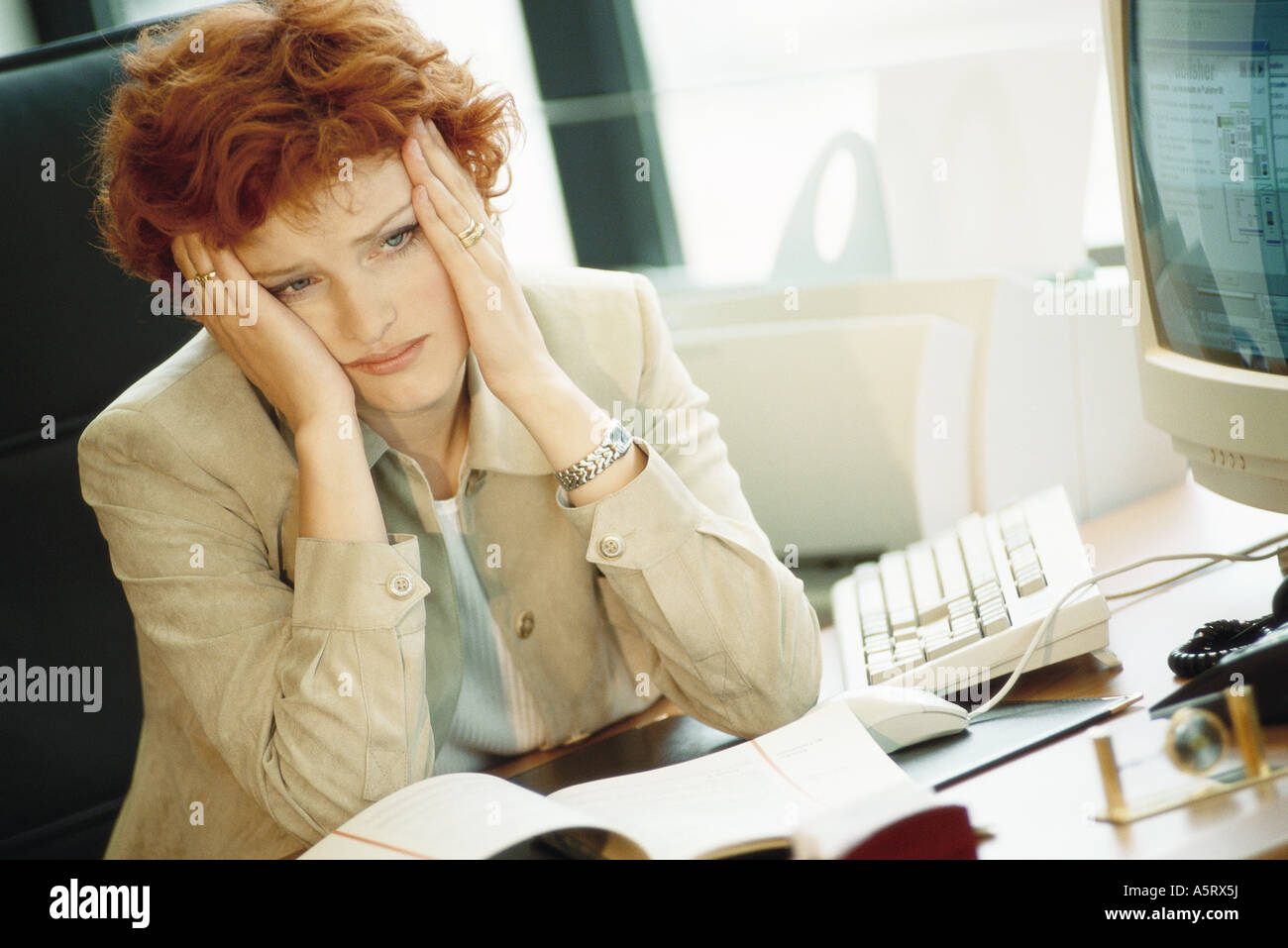 Businesswoman sitting at desk, holding head - Stock Image