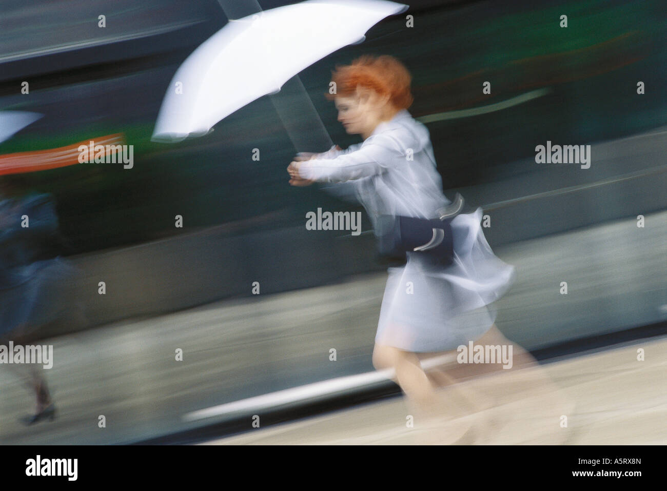 Businesswoman hurrying with umbrella - Stock Image