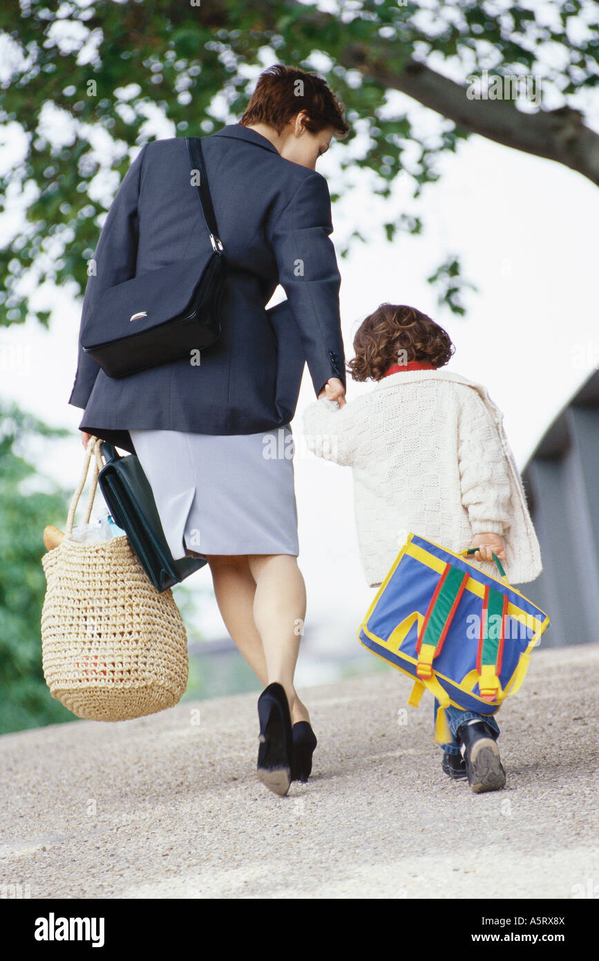 Businesswoman walking with son - Stock Image