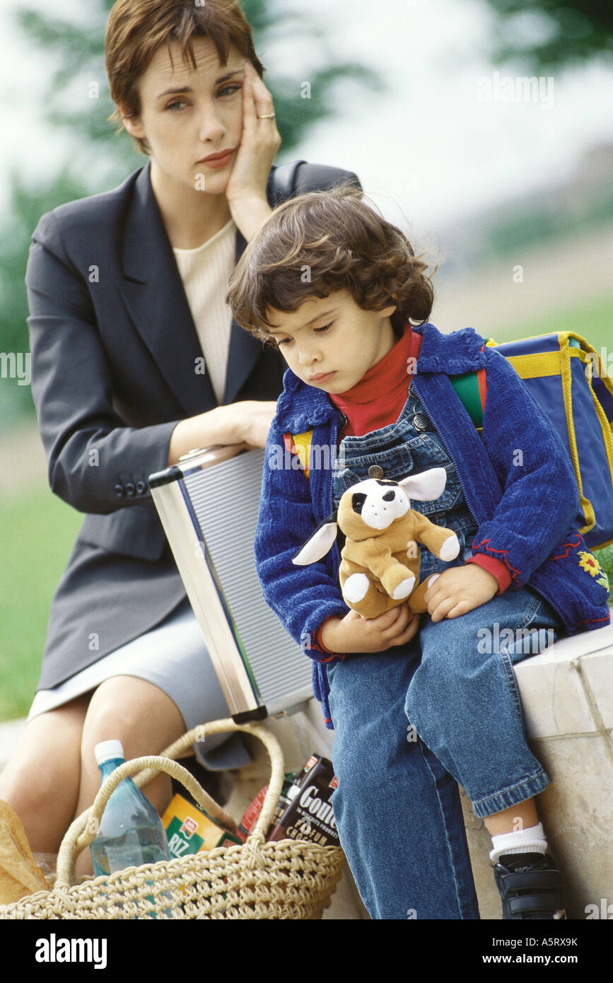 Businesswoman sitting with son, holding head - Stock Image