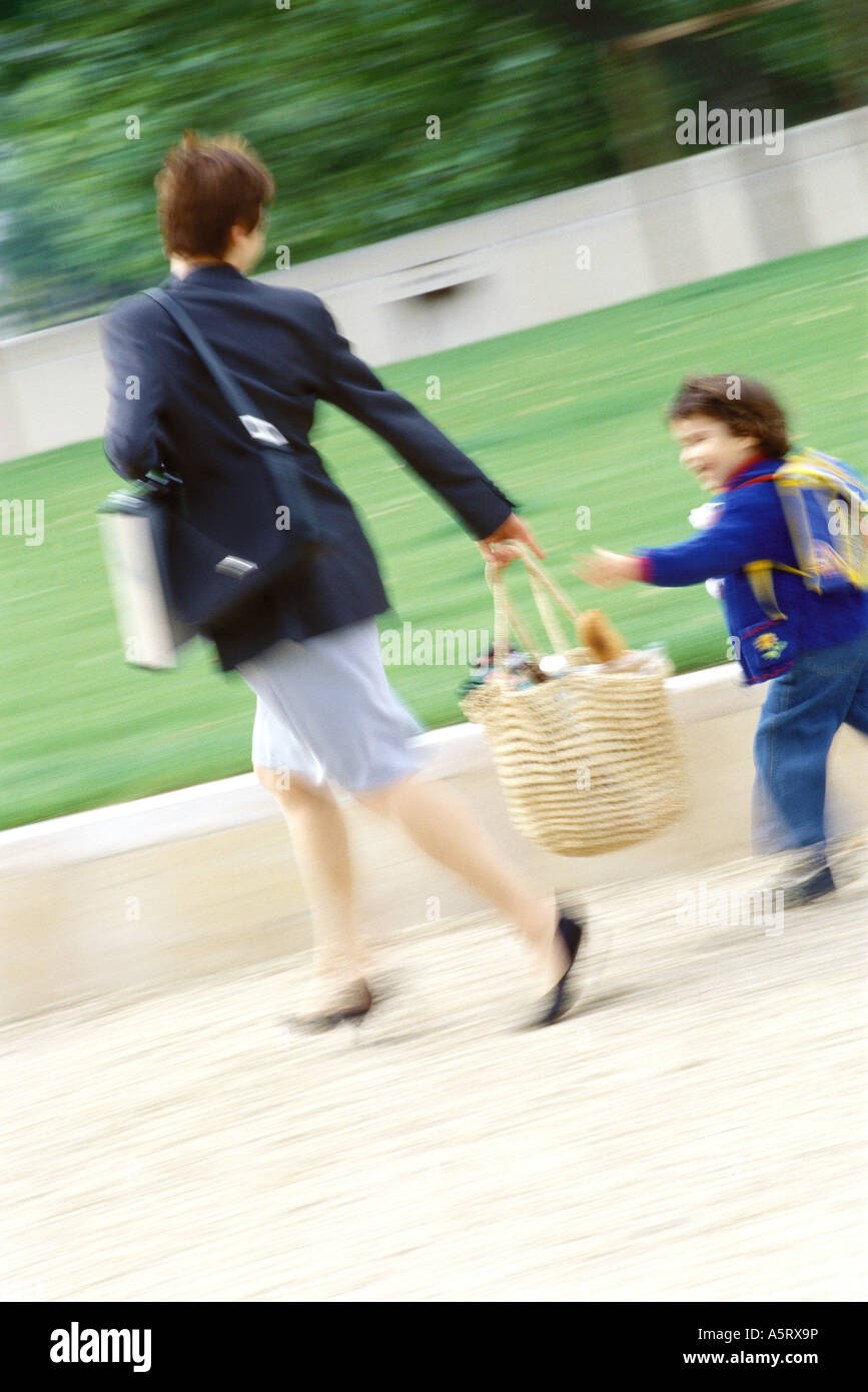 Businesswoman walking with son, blurred motion - Stock Image