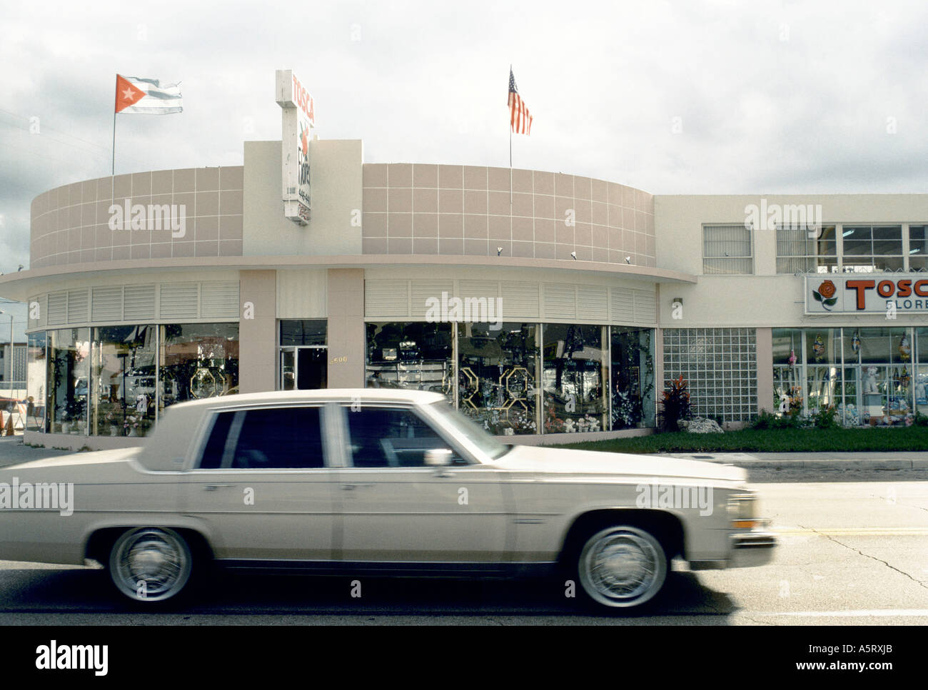 CUBAN EXILE COMMUNITY MIAMI STREET SCENE OF MIAMI S LITTLE HAVANA A WHITE CAR DEING DROVE PASS A FLOWER SHOP Stock Photo