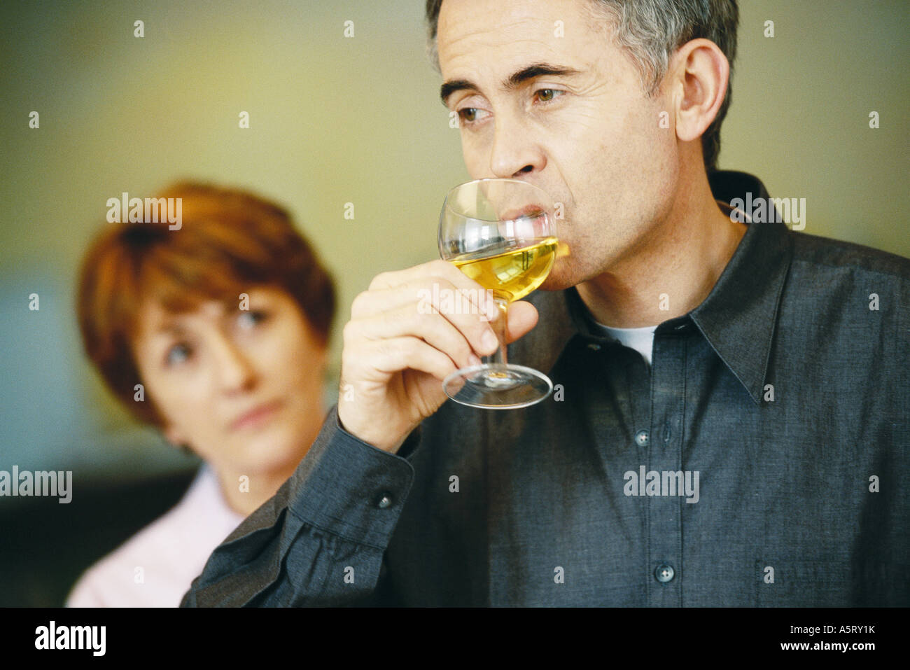 Senior man drinking glass of wine, senior woman looking at him in background - Stock Image
