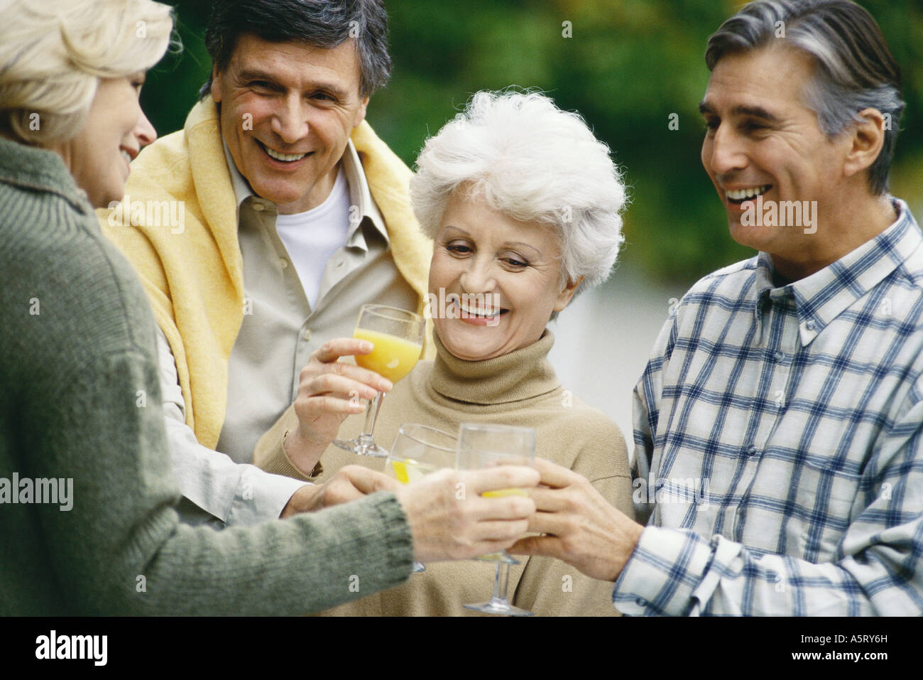 Two senior couples drinking orange juice and talking - Stock Image