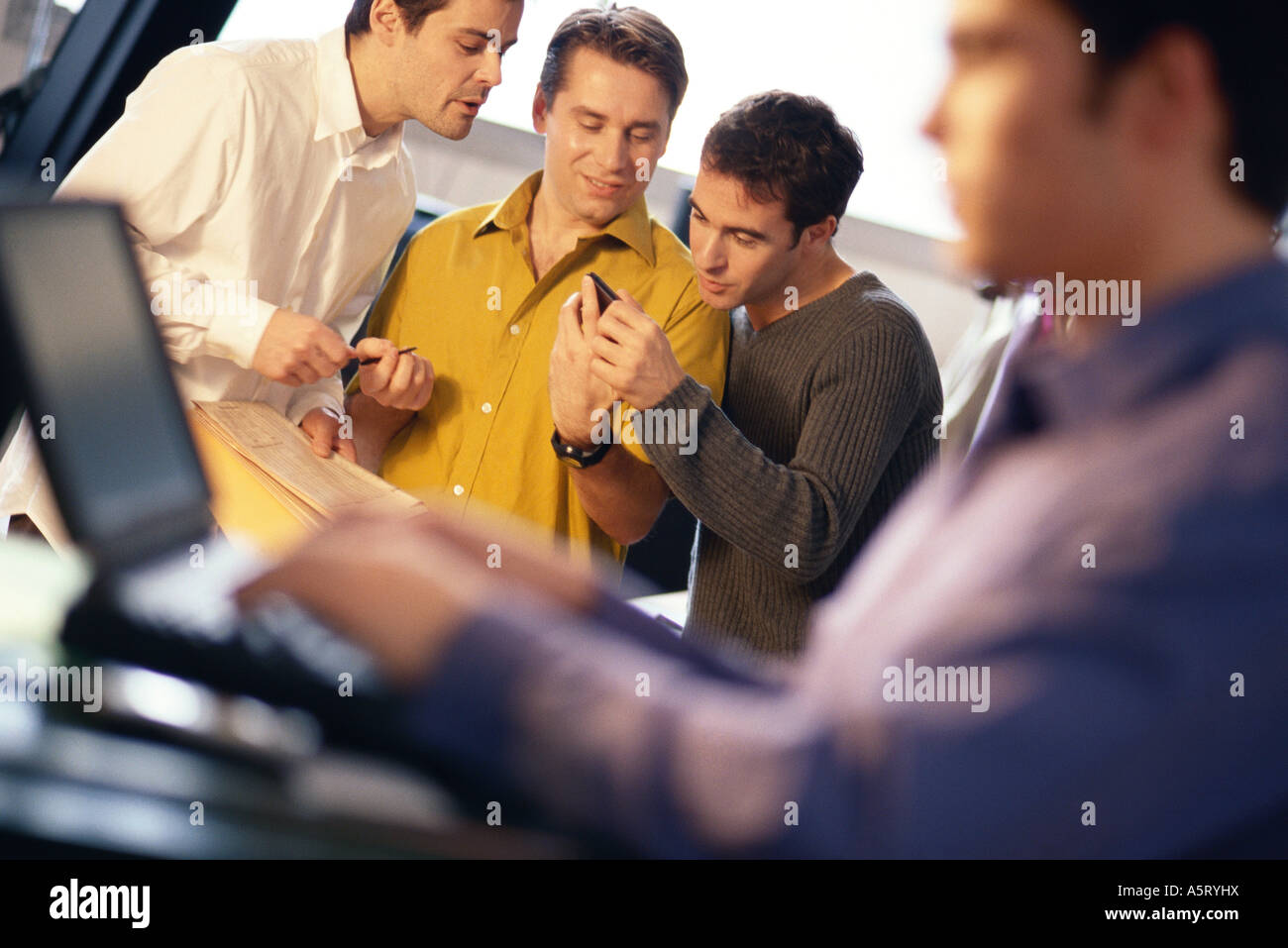 Three young men using electronic organizer, laptop user in foreground - Stock Image