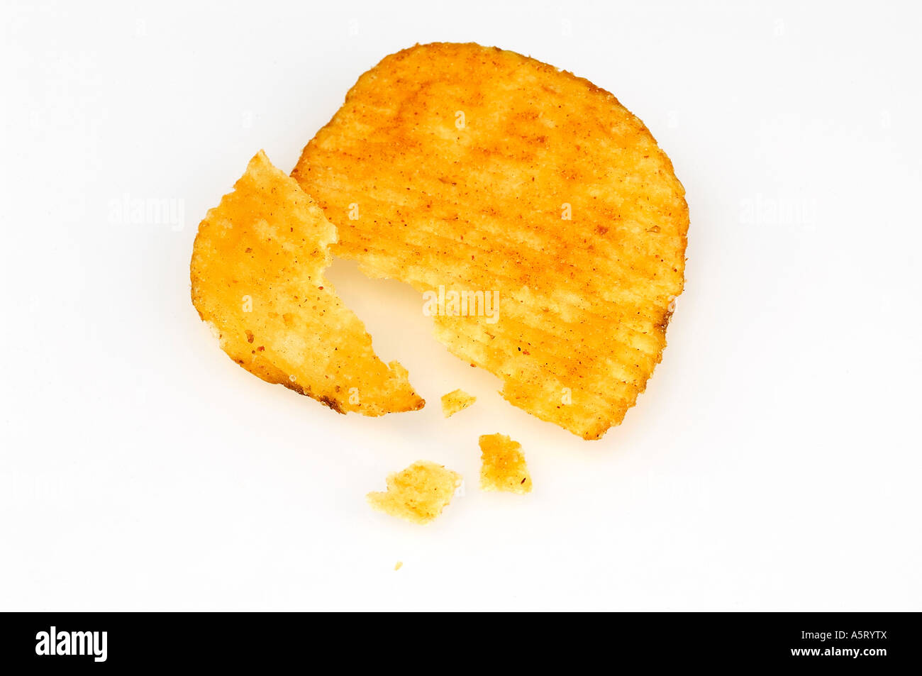 Broken flake of crisps and crumbs on white background - Stock Image