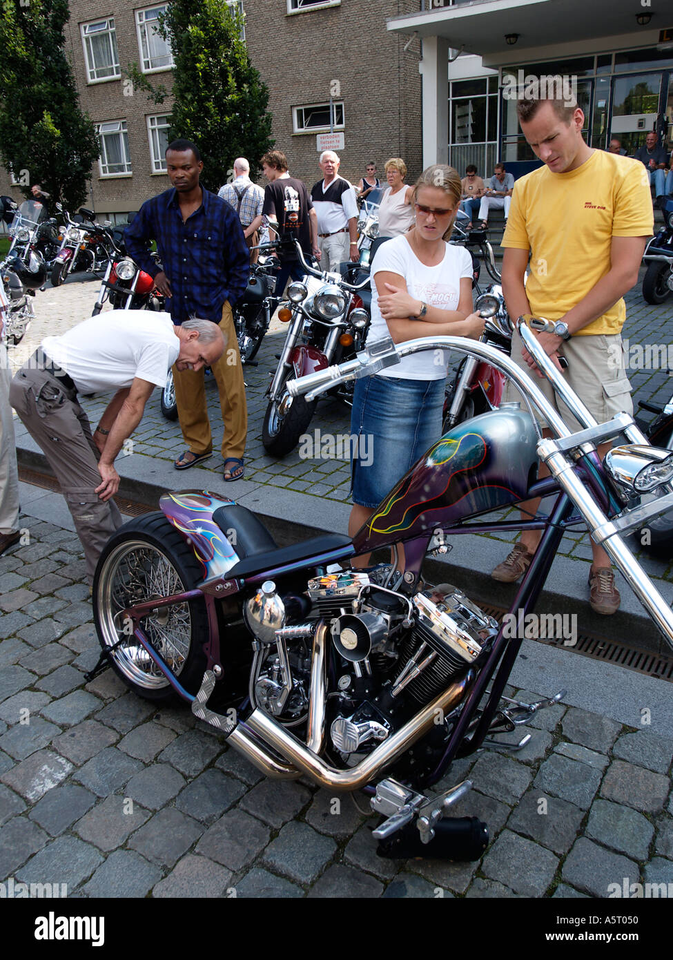 People admiring a custom built Harley Davidson chopper with a very radical design - Stock Image