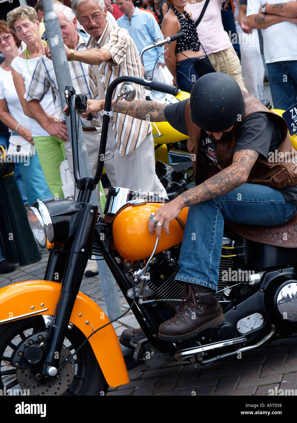 a heavily tattooed biker putting his orange classic chopper motorcycle in first gear with people looking - Stock Image