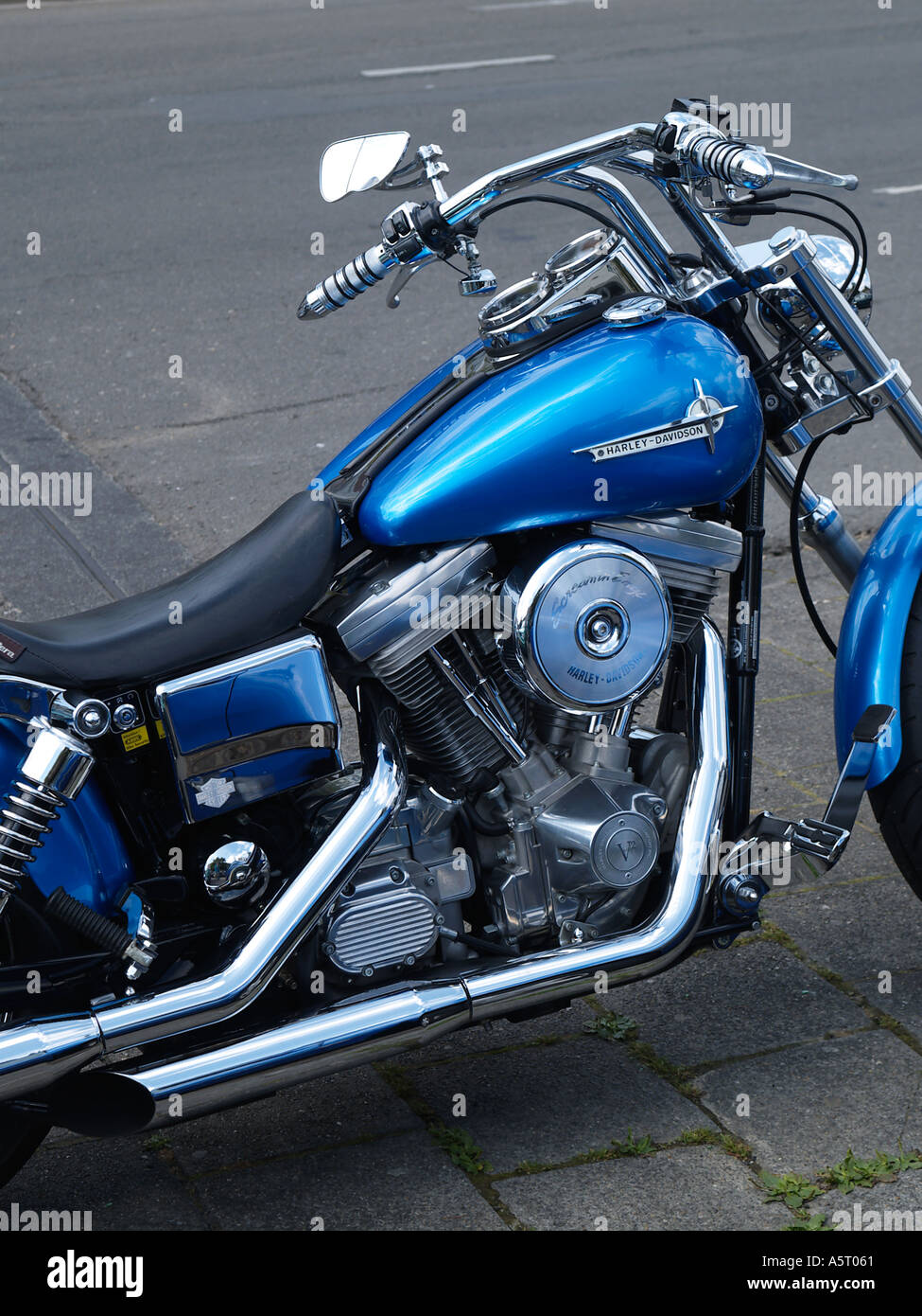 Electric blue Harley Davidson custom chopper parked by the roadside - Stock Image