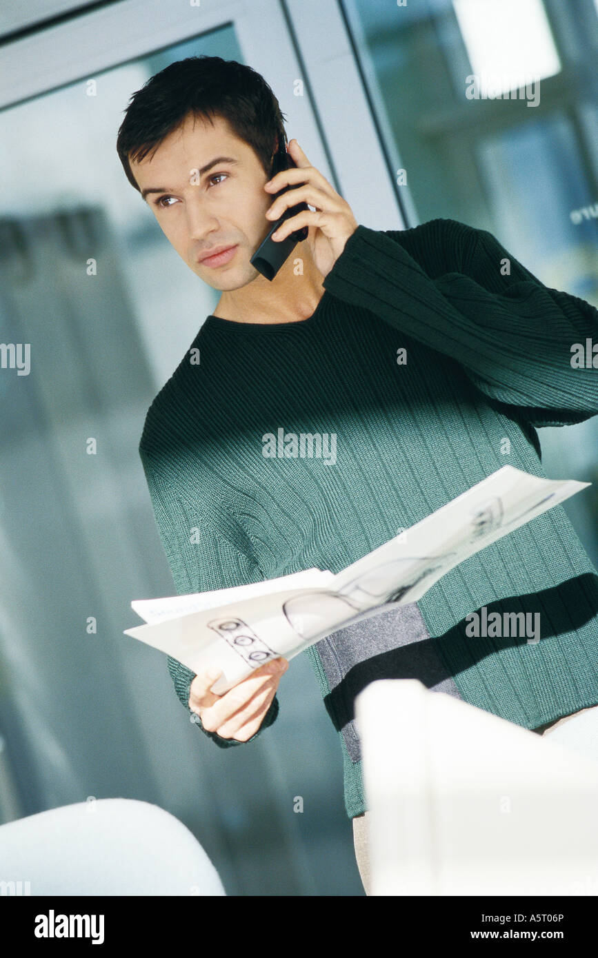 Young male office worker holding document, using telephone - Stock Image