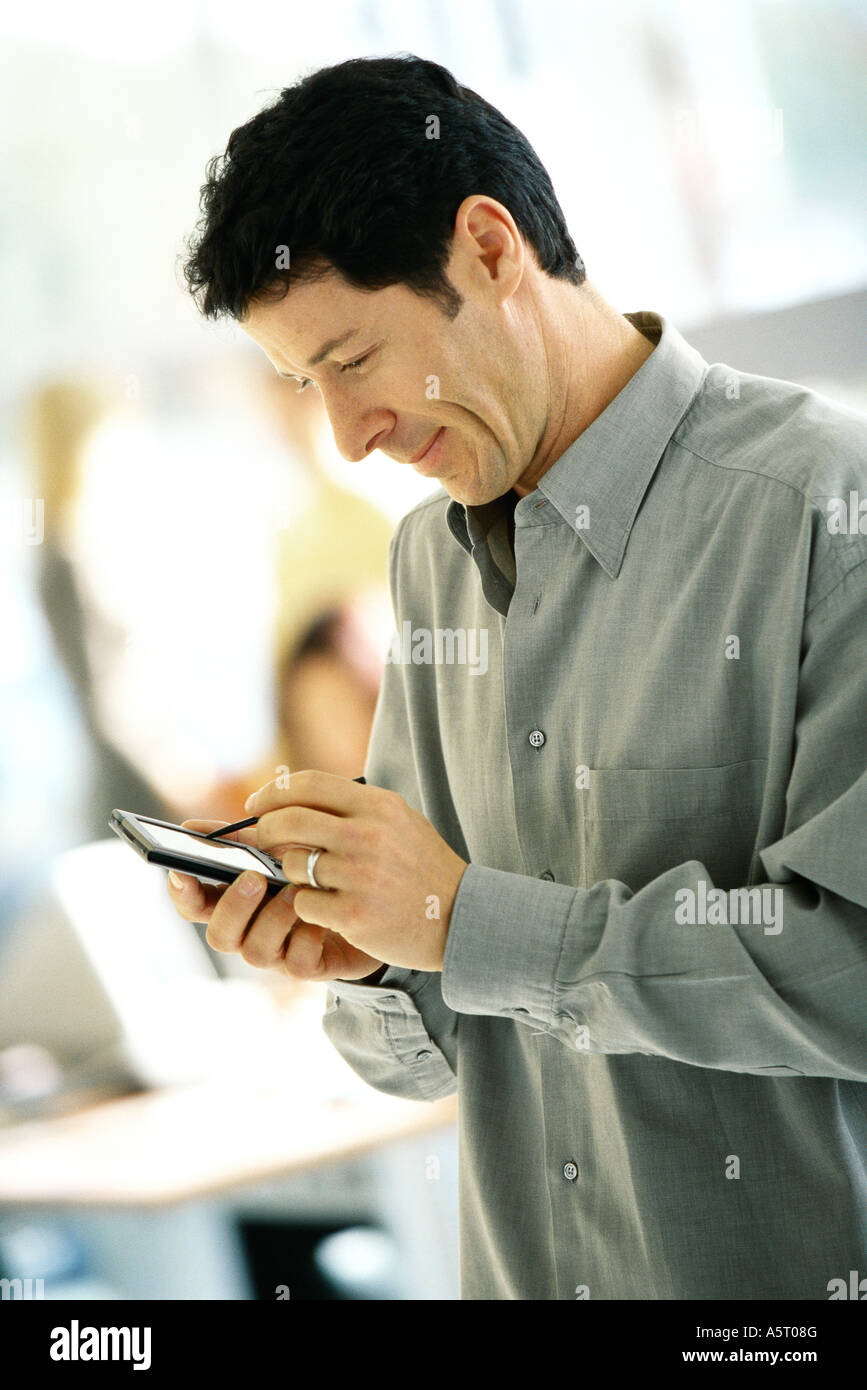 Man using electronic organizer, side view - Stock Image