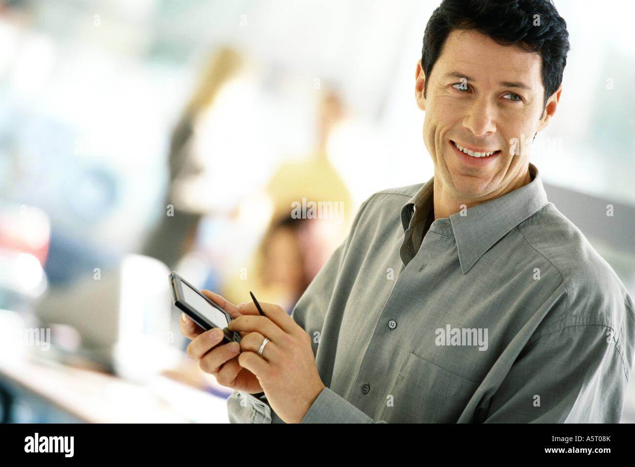 Man using electronic organizer, smiling - Stock Image
