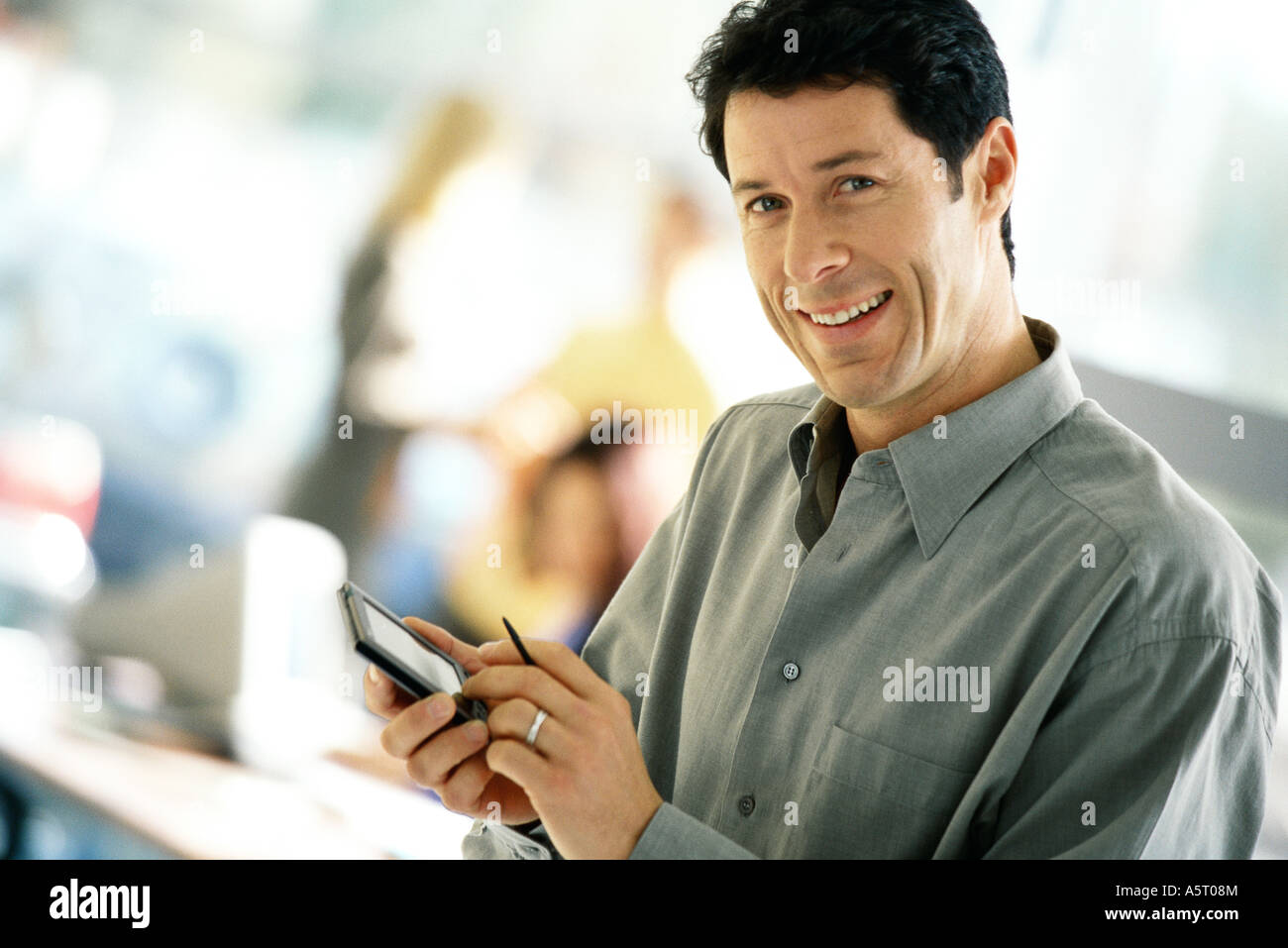 Man using electronic organizer, smiling at camera - Stock Image