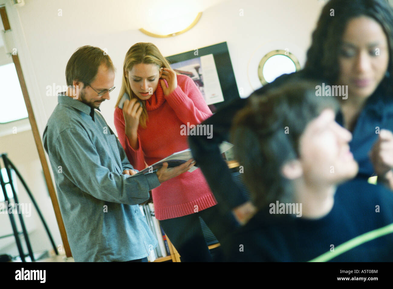 Man and woman looking at catalog, second man and woman in foreground - Stock Image