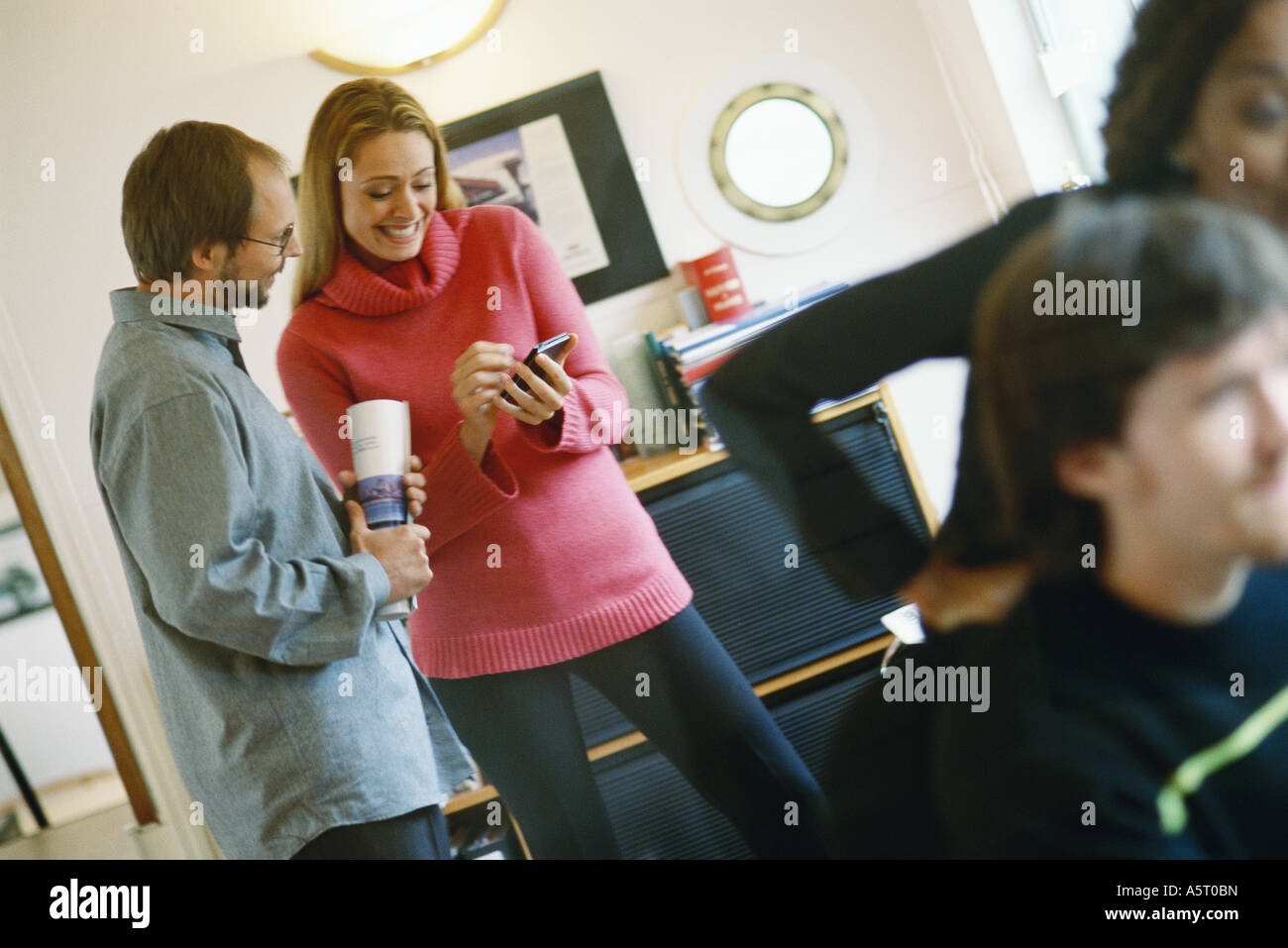 Man and woman using electronic organizer, second man and woman in foreground Stock Photo