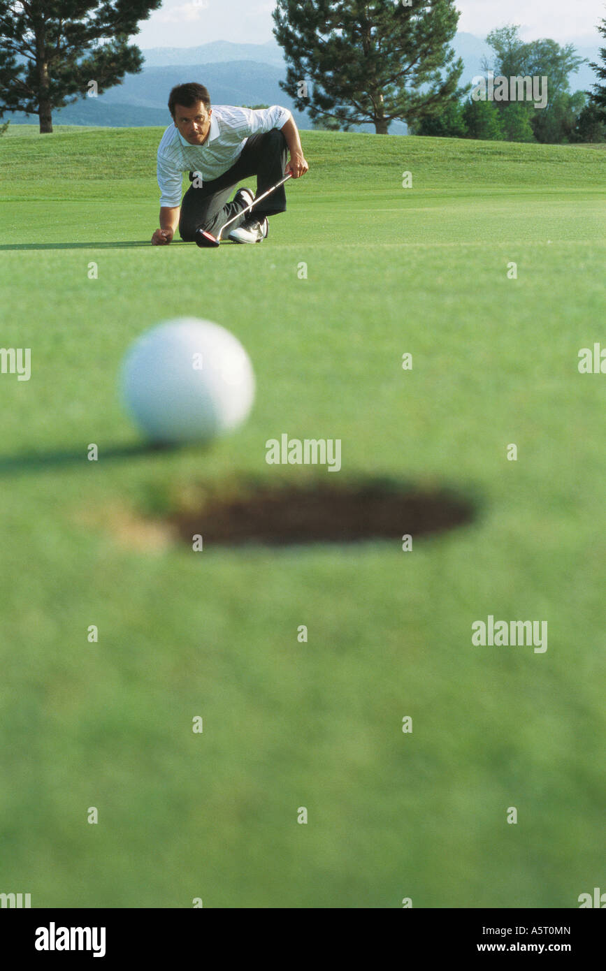 Golf ball at edge of hole, golfer in background squatting down, watching ball - Stock Image