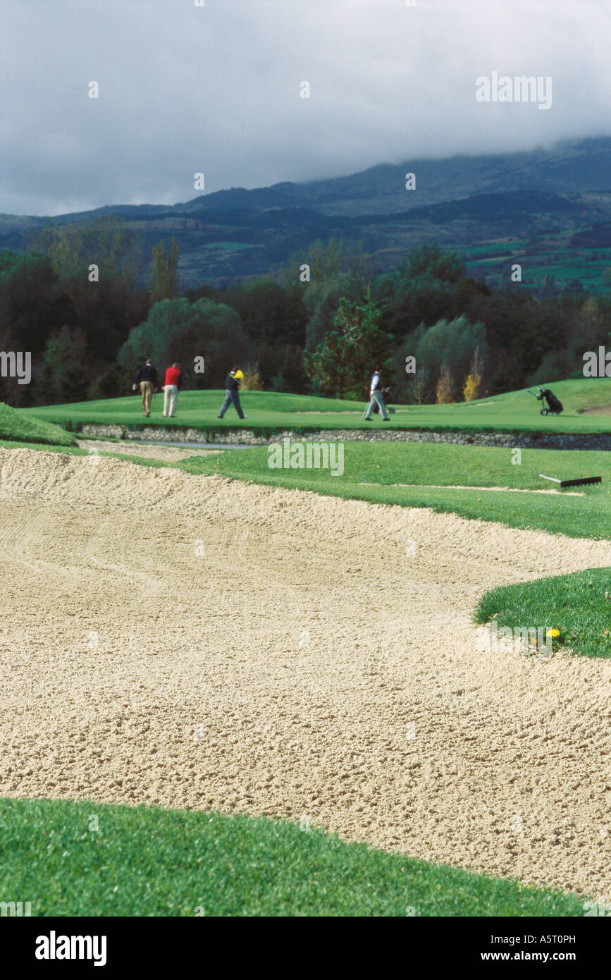 Golfers on golf course, sand trap in foreground - Stock Image