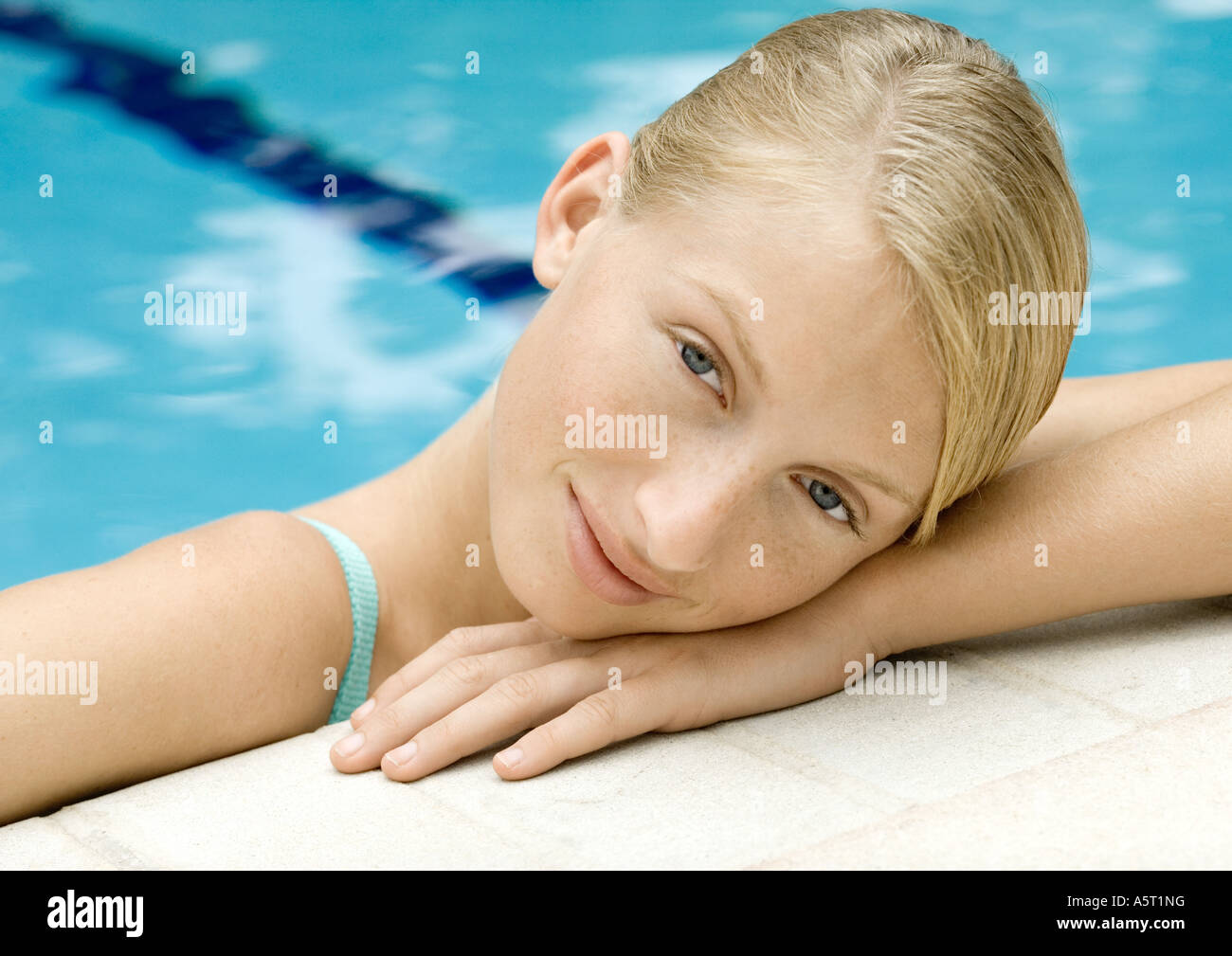 Young woman resting head on edge of pool - Stock Image