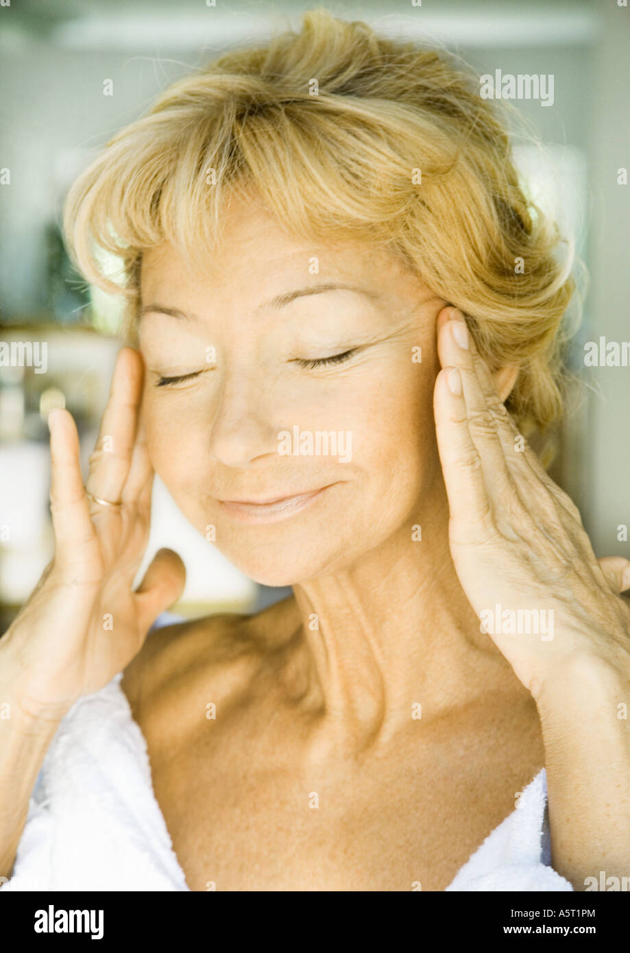 Senior woman with hands on side of face and eyes shut - Stock Image