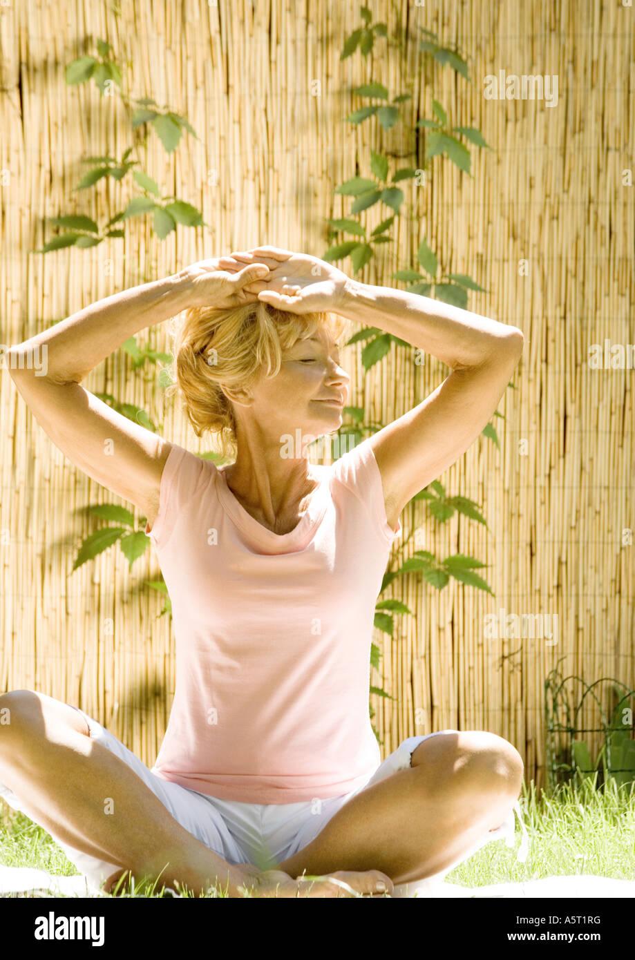 Senior woman doing exercise outdoors - Stock Image